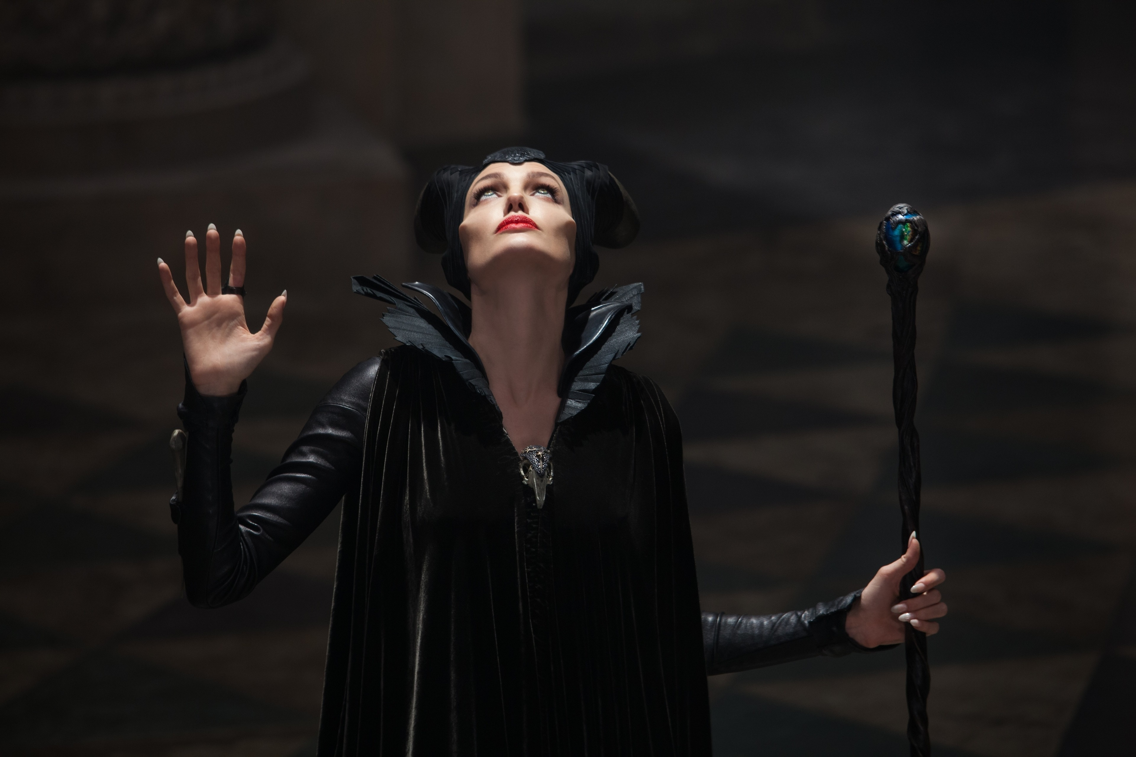 """Angelina Jolie as Maleficent, staff in hand, looking up at the light in the movie """"Maleficent"""""""