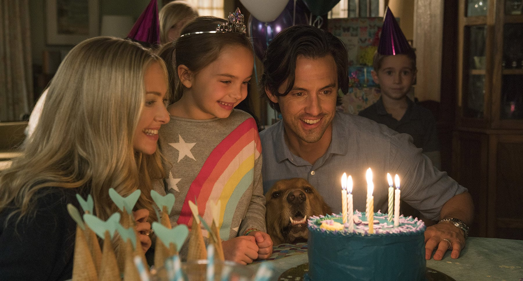 "Denny (Milo Ventimiglia), Eve (Amanda Seyfried), dog Enzo and Zoë (Ryan Kiera Armstrong) looking at a birthday cake in the movie ""The Art of Racing in the Rain"""
