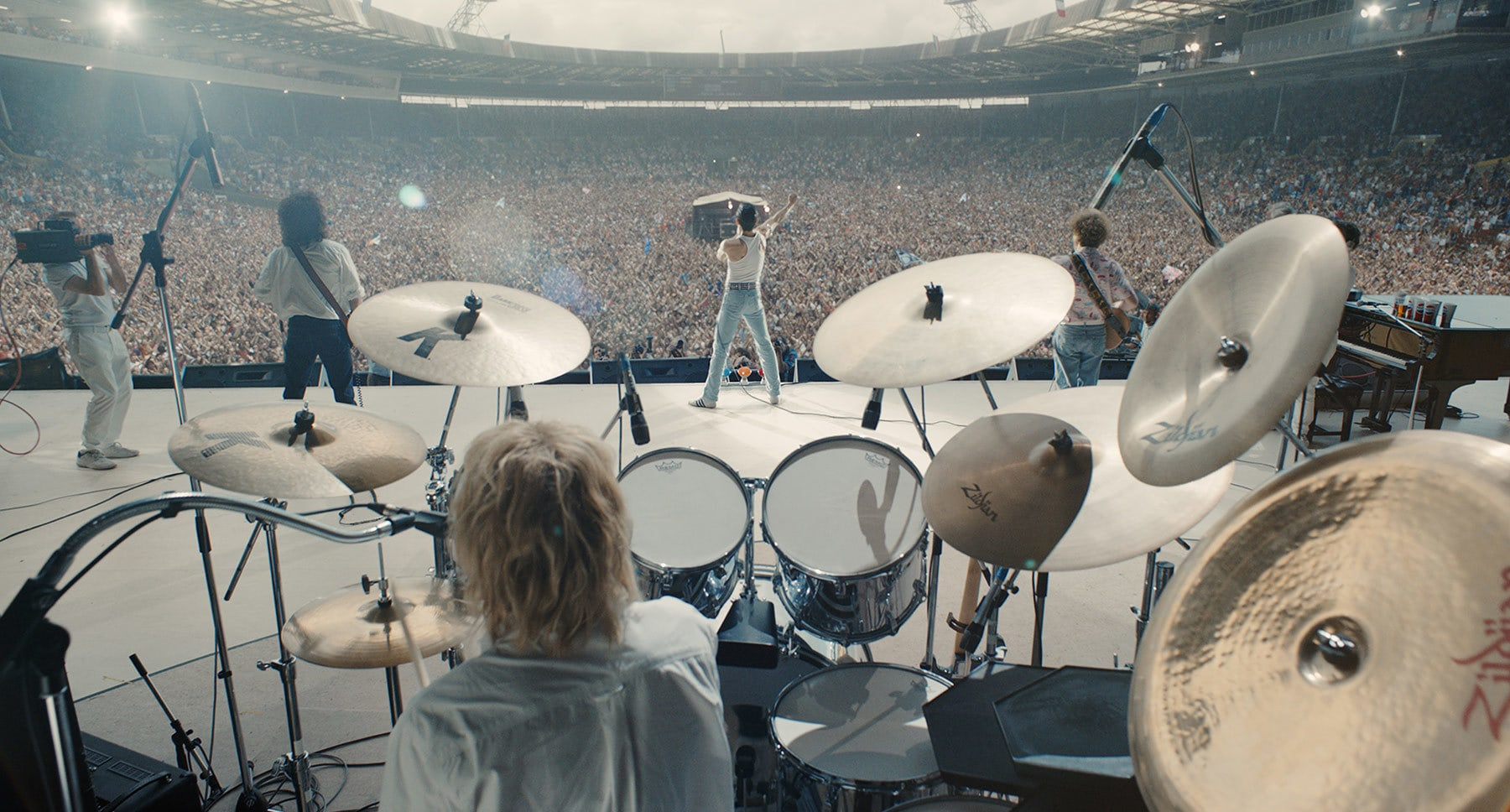 "Rami Malek (as Freddie Mercury) Gwilym Lee (as Brian May), Ben Hardy (as Roger Taylor), and Joseph Mazzello (as John Deacon) on large concert stage in front of a large crowd in the movie ""Bohemian Rhapsody"""