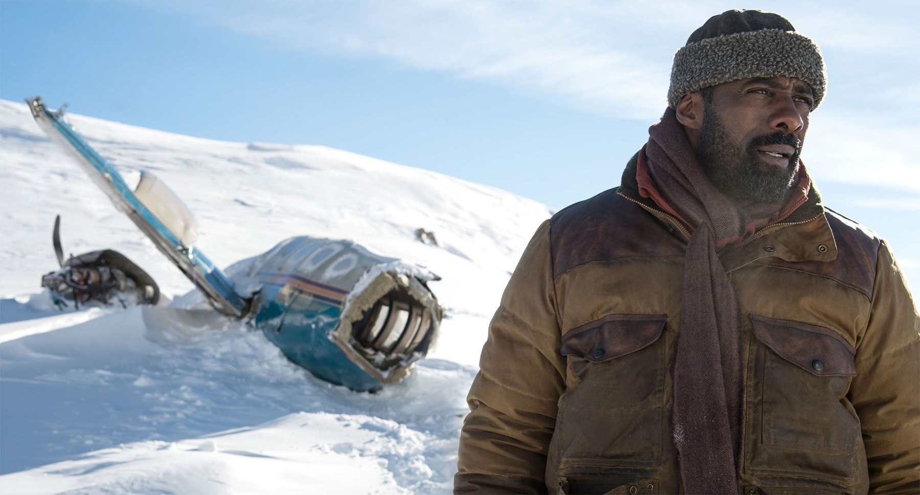 "Idris Elba (as Ben Bass) near plane wreckage on a snowy mountain in the movie ""The Mountain Between Us"""