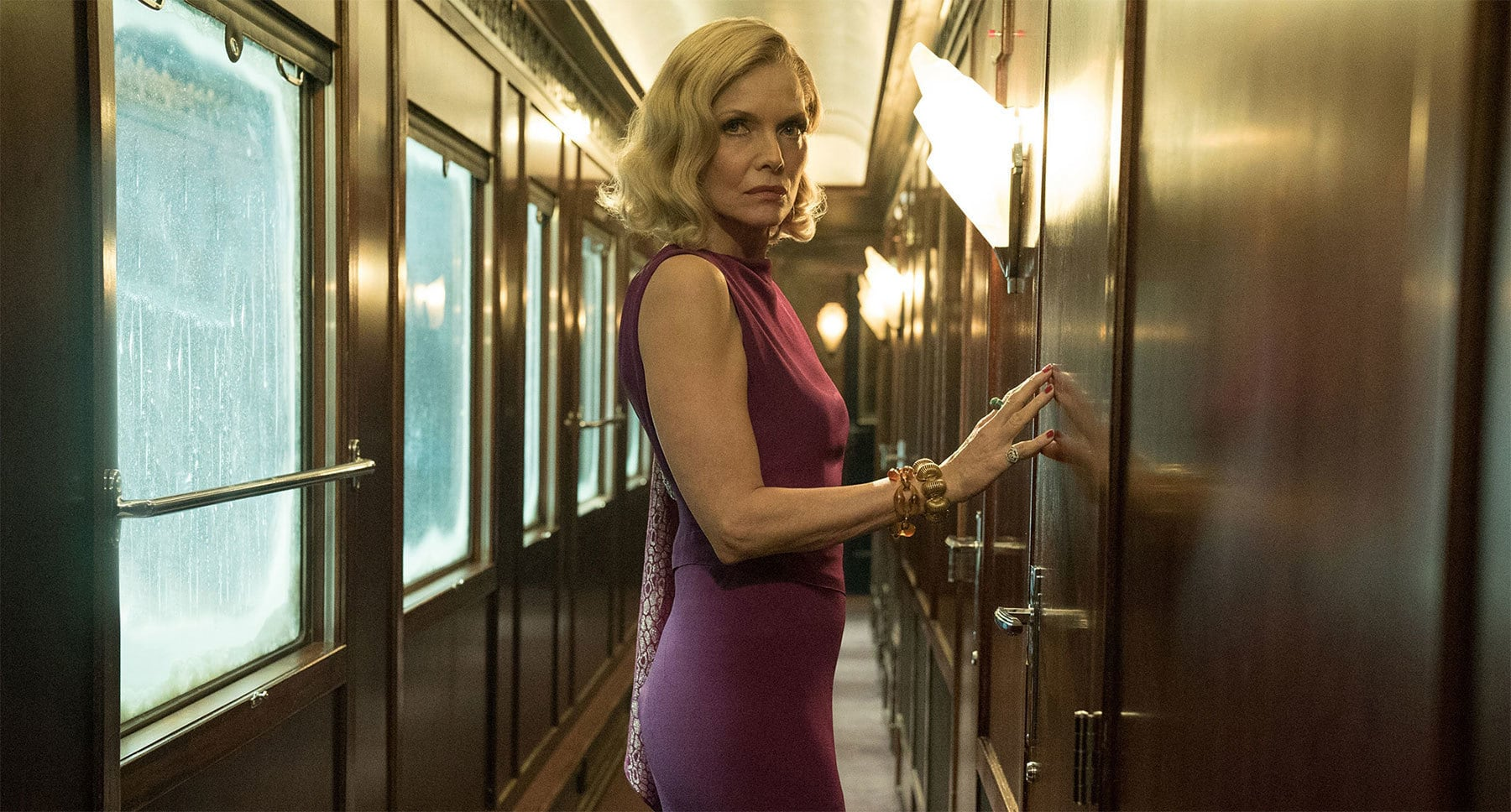 "Michelle Pfeiffer (as Caroline Hubbard) standing a room on the train in ""Murder on the Orient Express"""