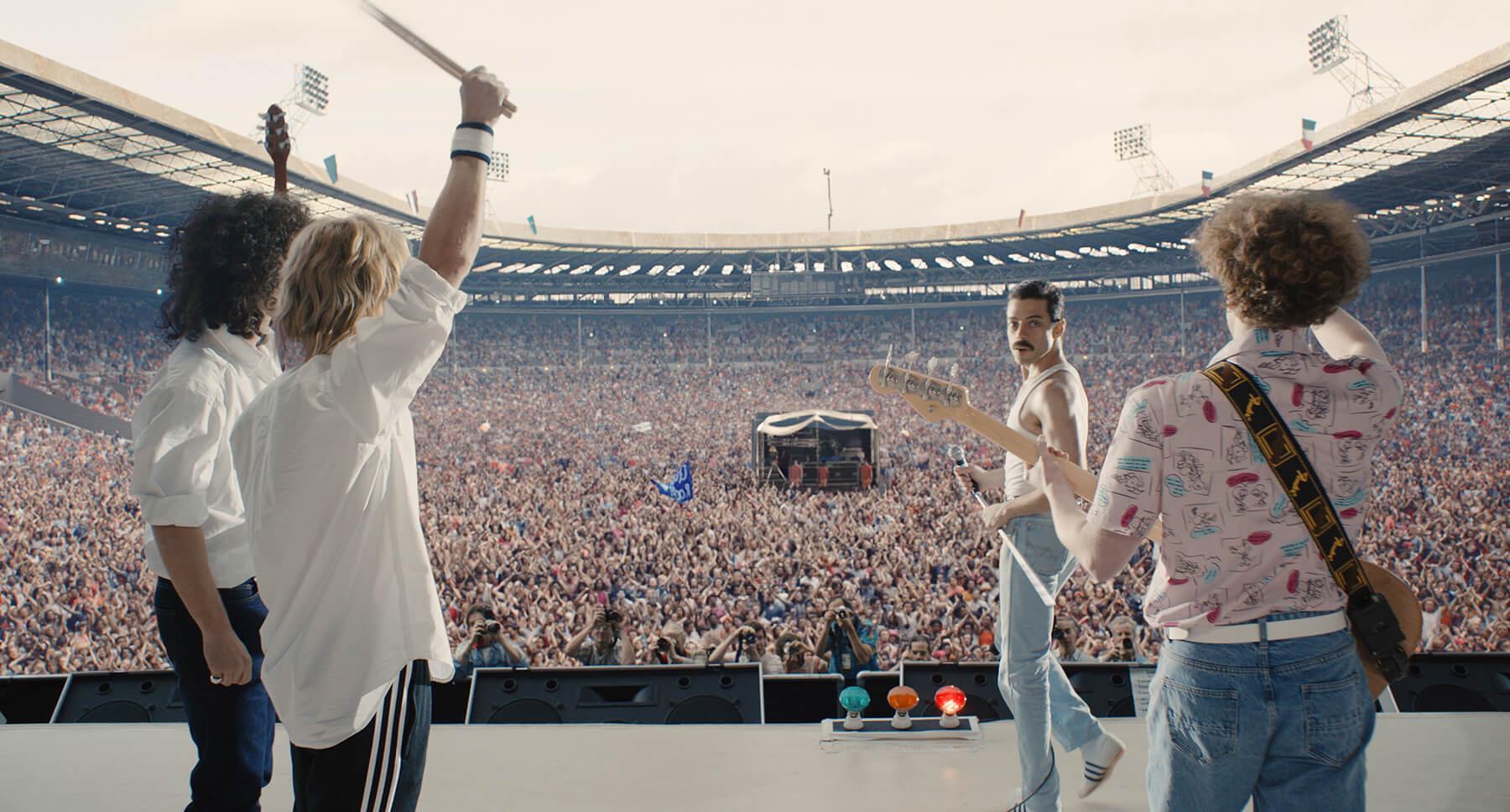 "Actor Rami Malek (as Freddie Mercury) standing in front of a concert crowd in the movie ""Bohemian Rhapsody"""