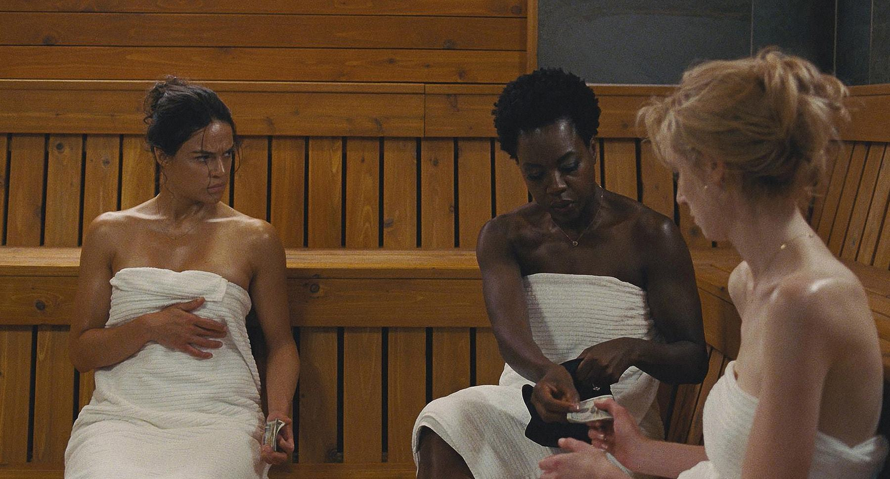 "Viola Davis, Michelle Rodriguez, and Elizabeth Debicki sitting in a sauna in ""Widows"""