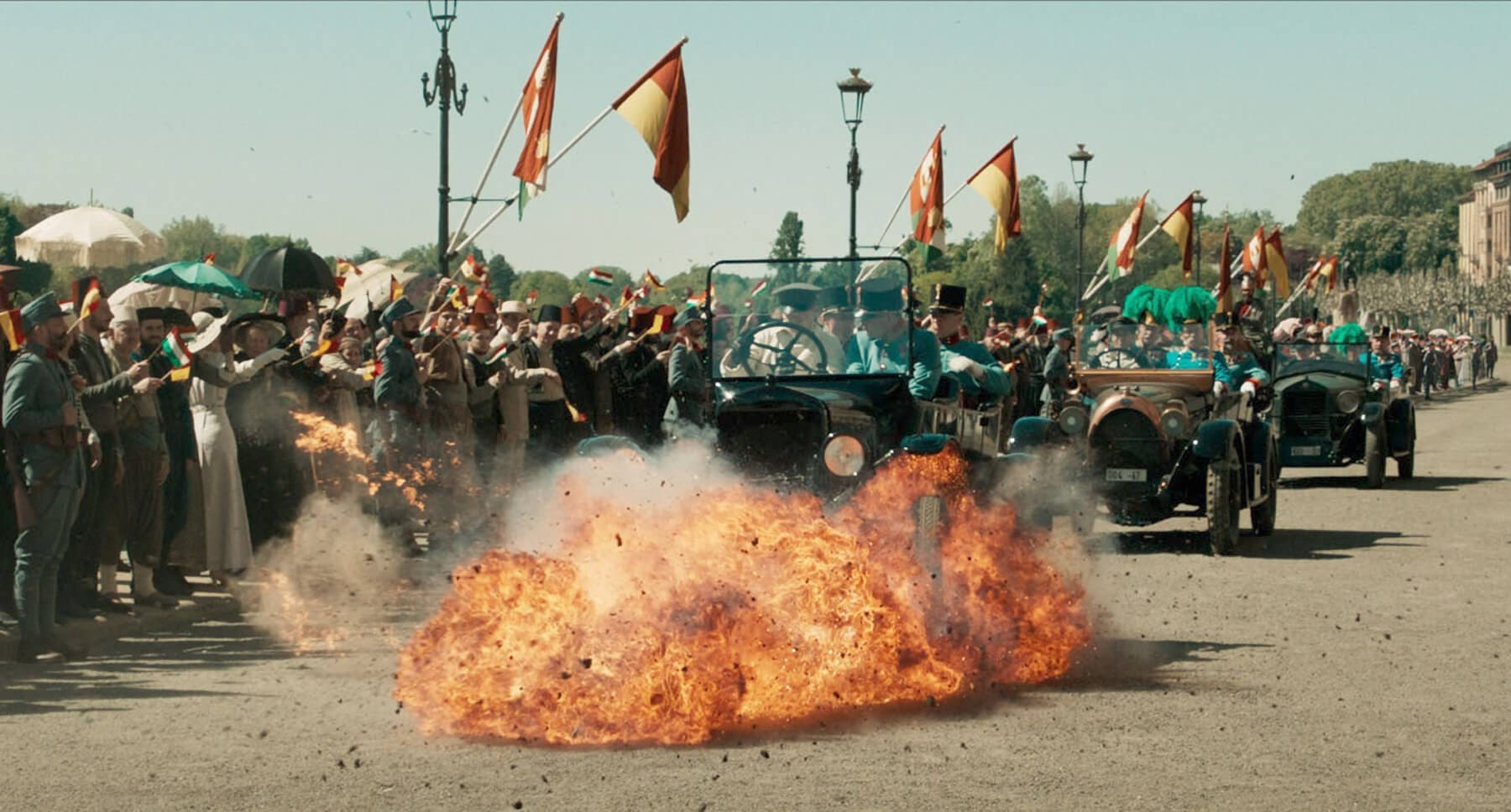"A car driving through fire in a scene from the movie ""The King's Man"""