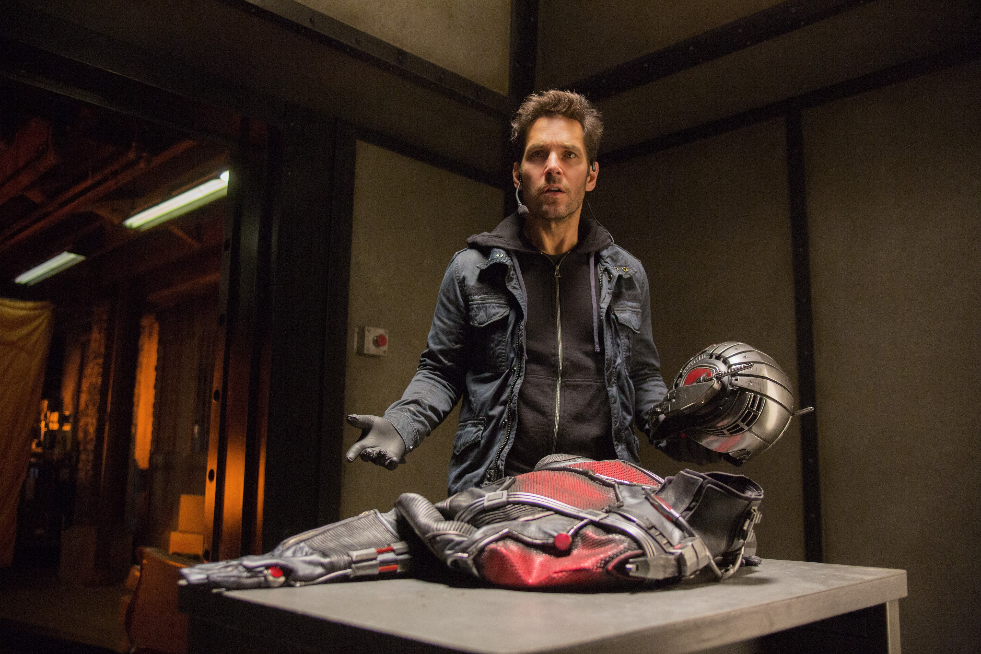 Paul Rudd (as Scott Lang) posing in front of the Ant-Man suit