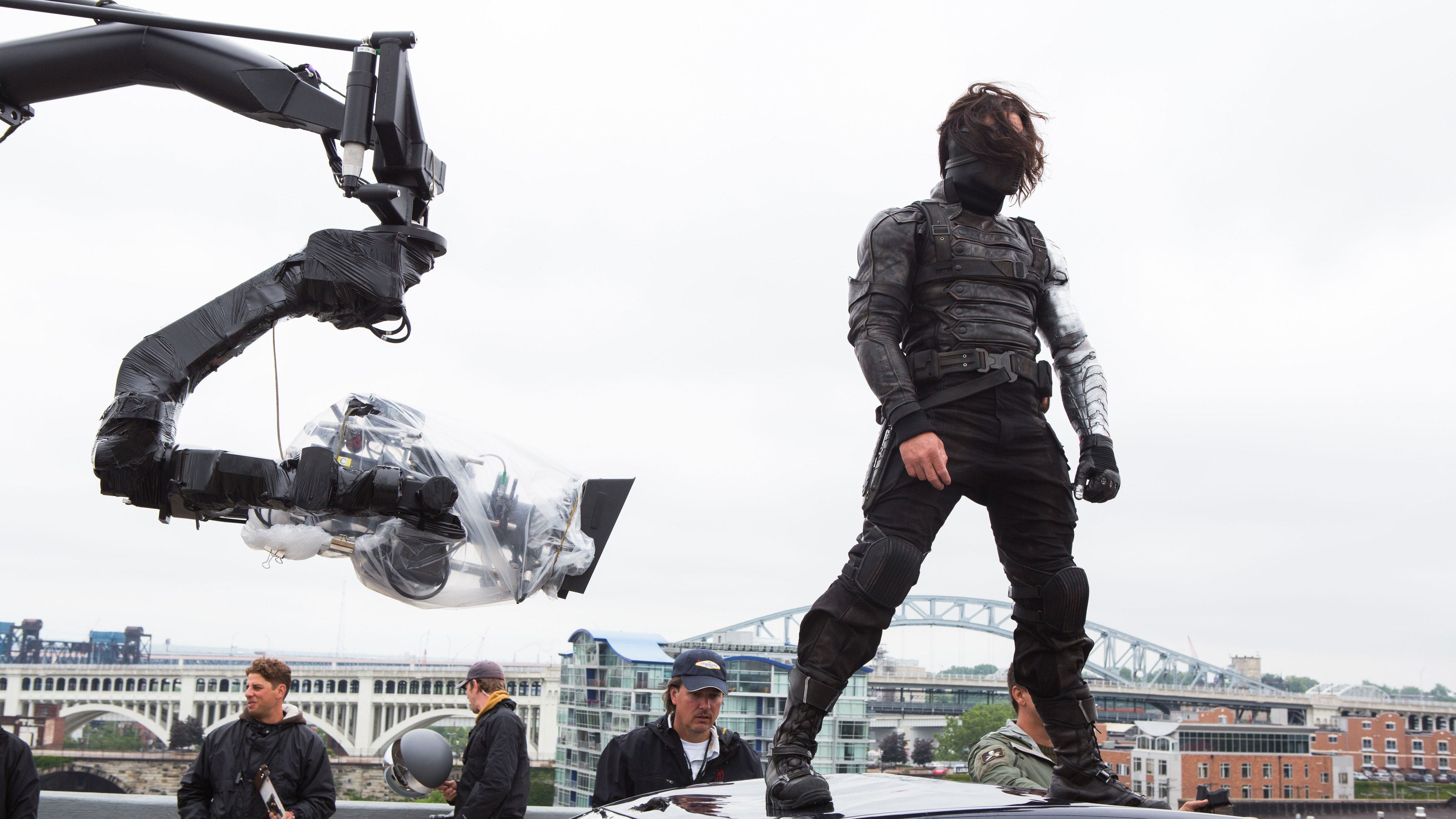 Actor Sebastian Stan (Bucky Barnes/Winter Soldier) behind-the-scenes on top of a car in Captain America: The Winter Soldier.