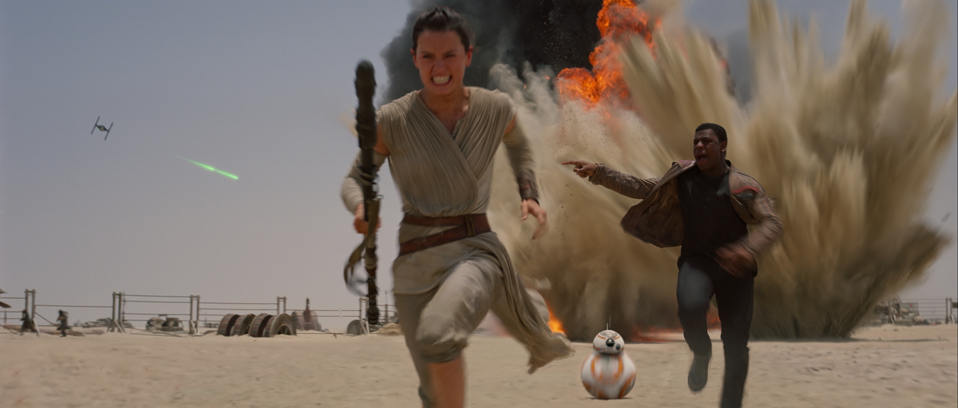 Daisy Ridley as Rey, Joh Boyega as Finn, and BB-8 on the running  from TIE fighters.