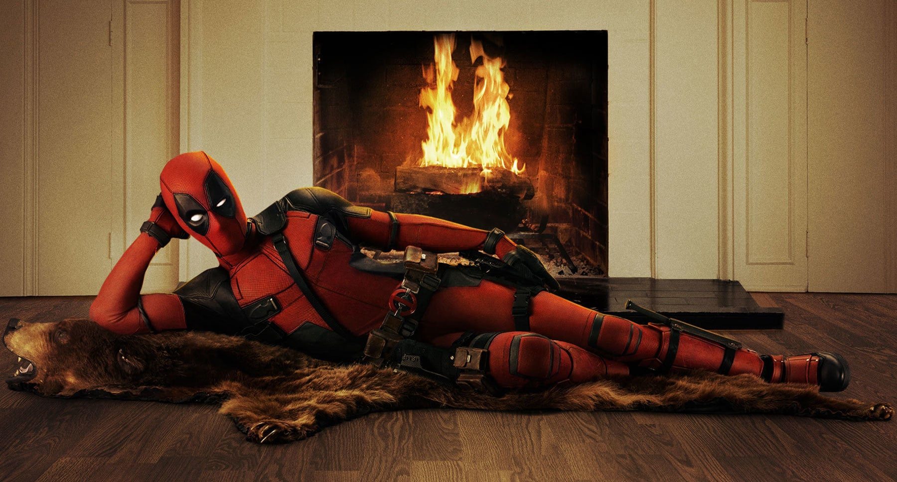 "Ryan Reynolds (as Deadpool) lounging on a rug next to a fireplace in ""Deadpool"""