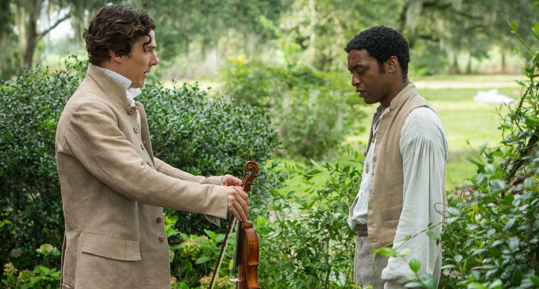 "Actors Benedict Cumberbatch (Ford) handing Chiwetel Ejiofor (Solomon Northrup) a violin in the film ""12 Years A Slave"""