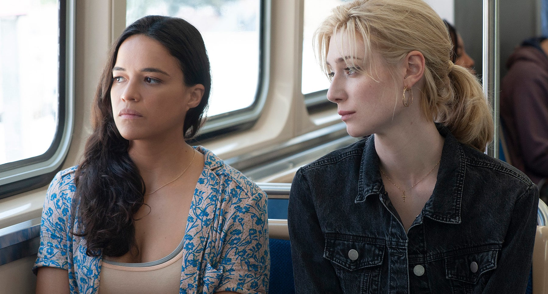 "Michelle Rodriguez and Elizabeth Debicki sitting in a bus from the movie ""Widows"""