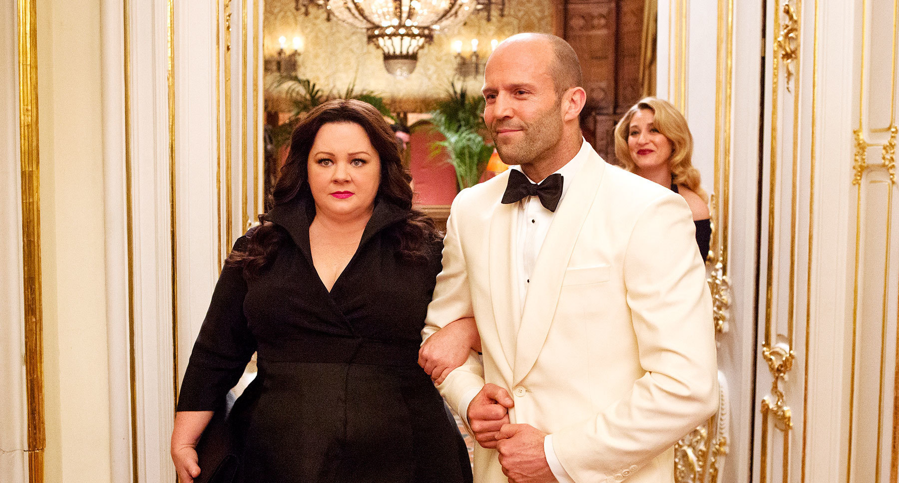 "Jason Statham (as Rick Ford) and Melissa McCarthy (as Susan Cooper) attends a party in ""Spy"""