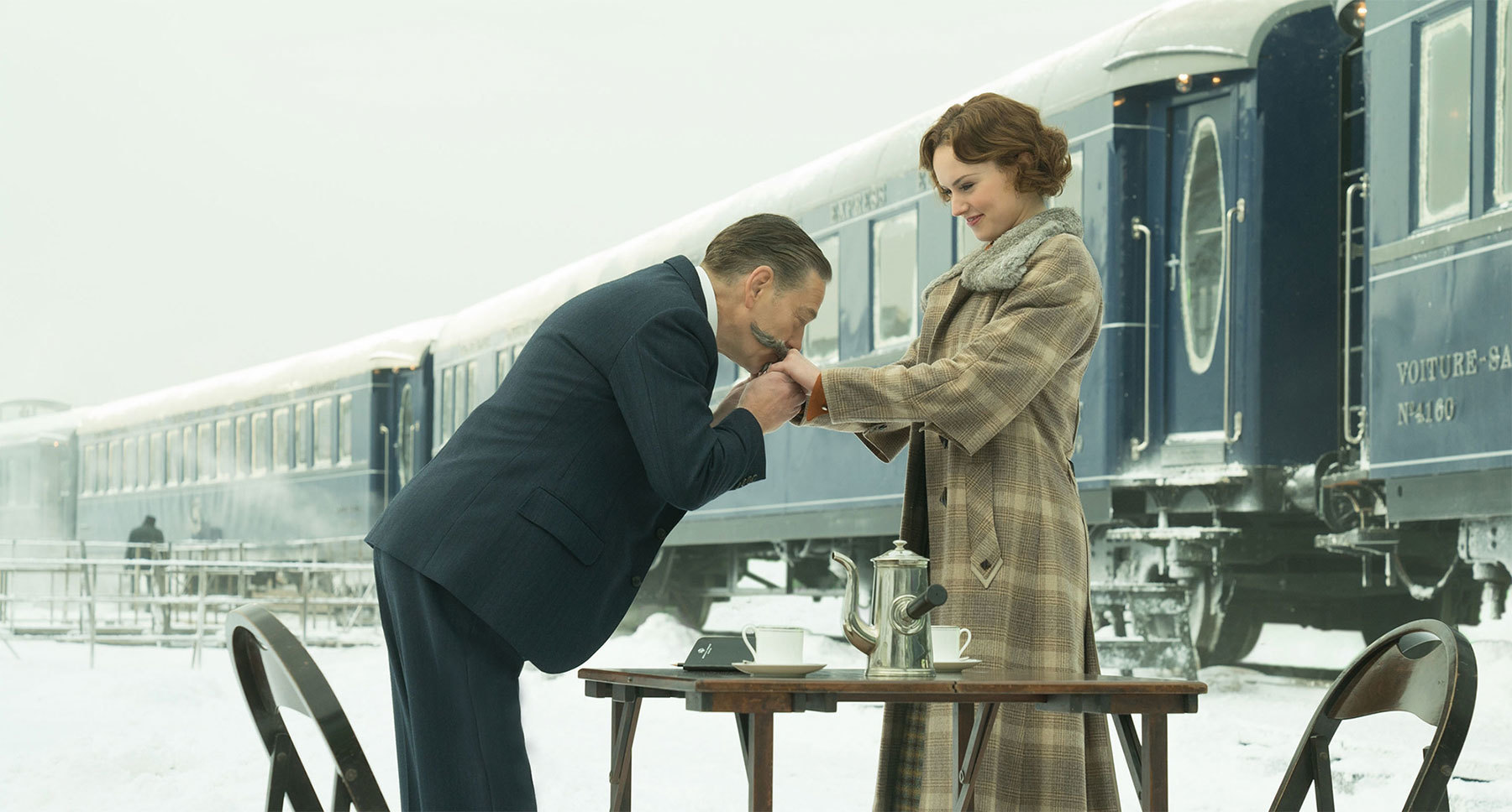 "Kenneth Branagh (as Hercule Poirot) kissing  Daisy Ridley (as Mary Debenham) hands at a table set in ""Murder on the Orient Express"""
