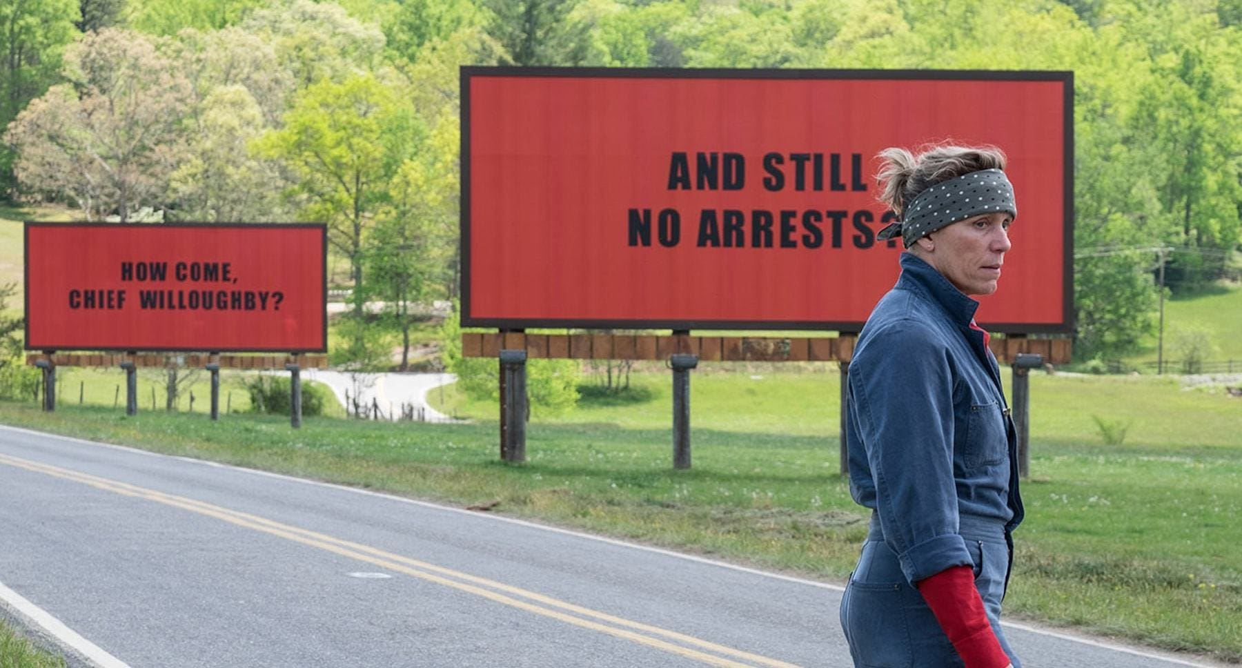 "Frances McDormand as Mildred standing next to billboards in ""Three Billboards Outside Ebbing, Missouri"""