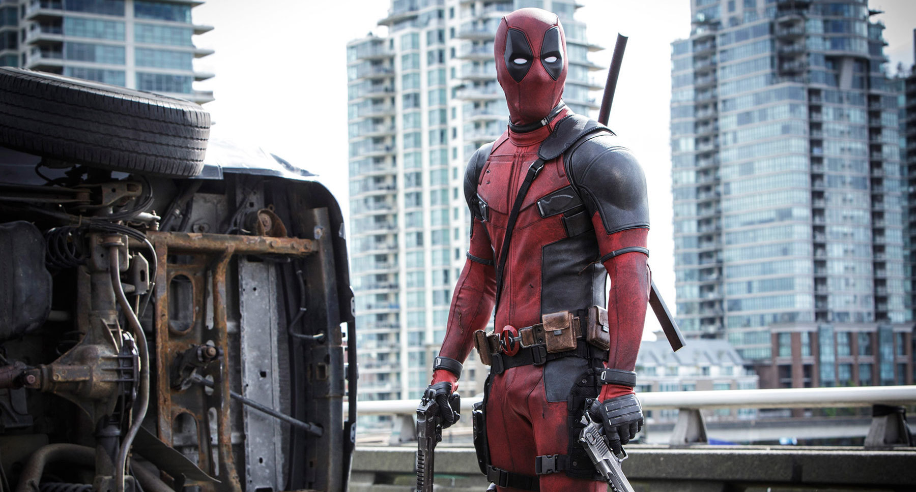 "Ryan Reynolds (as Deadpool) with guns in his hands standing next to an overturned vehicle in ""Deadpool"""