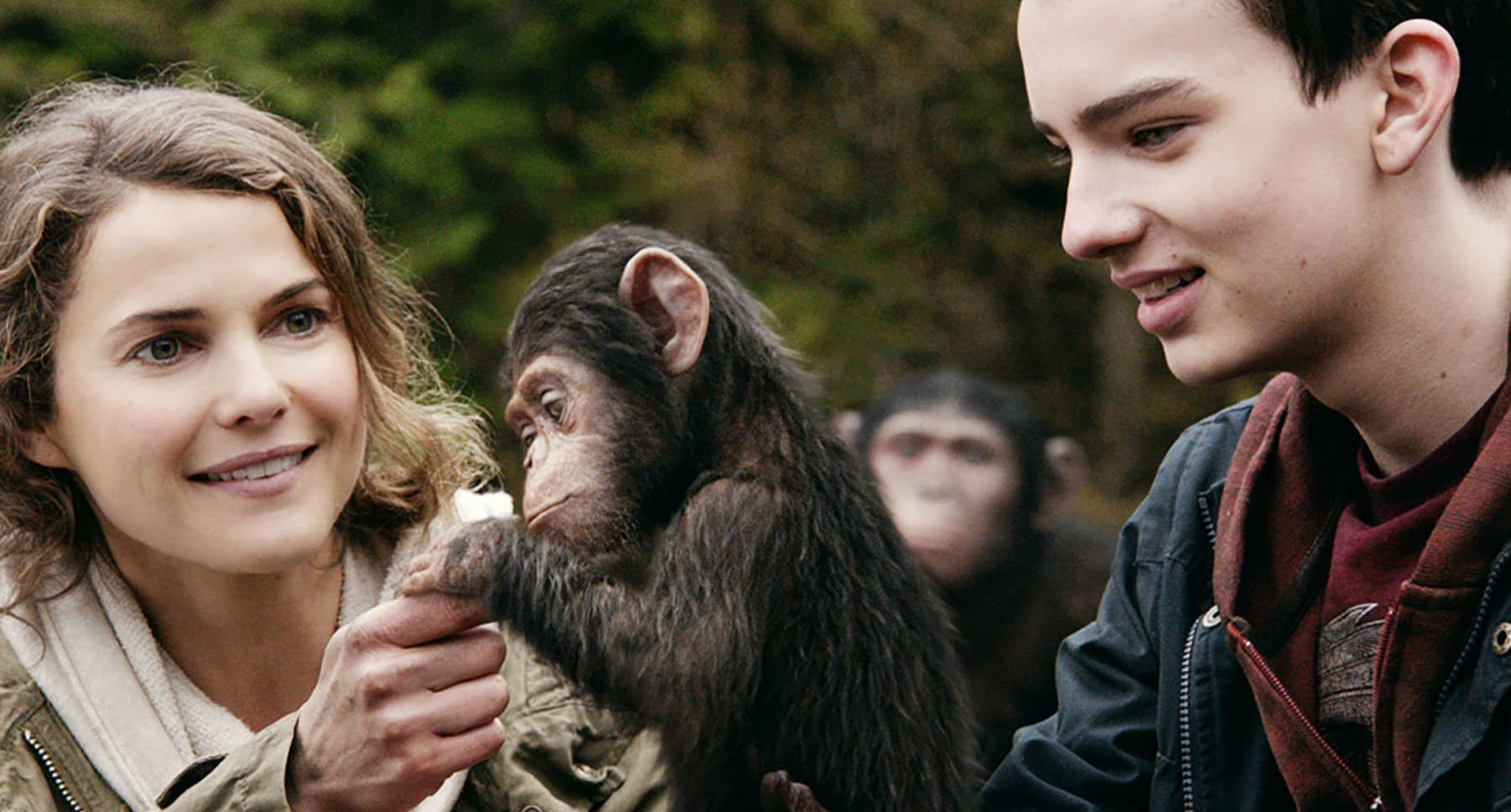 "Baby ape holds actor Keri Russell's finger as actor Kodi Smit-McPhee (as Alexander) watches in the film ""Dawn Of The Planet Of The Apes"""