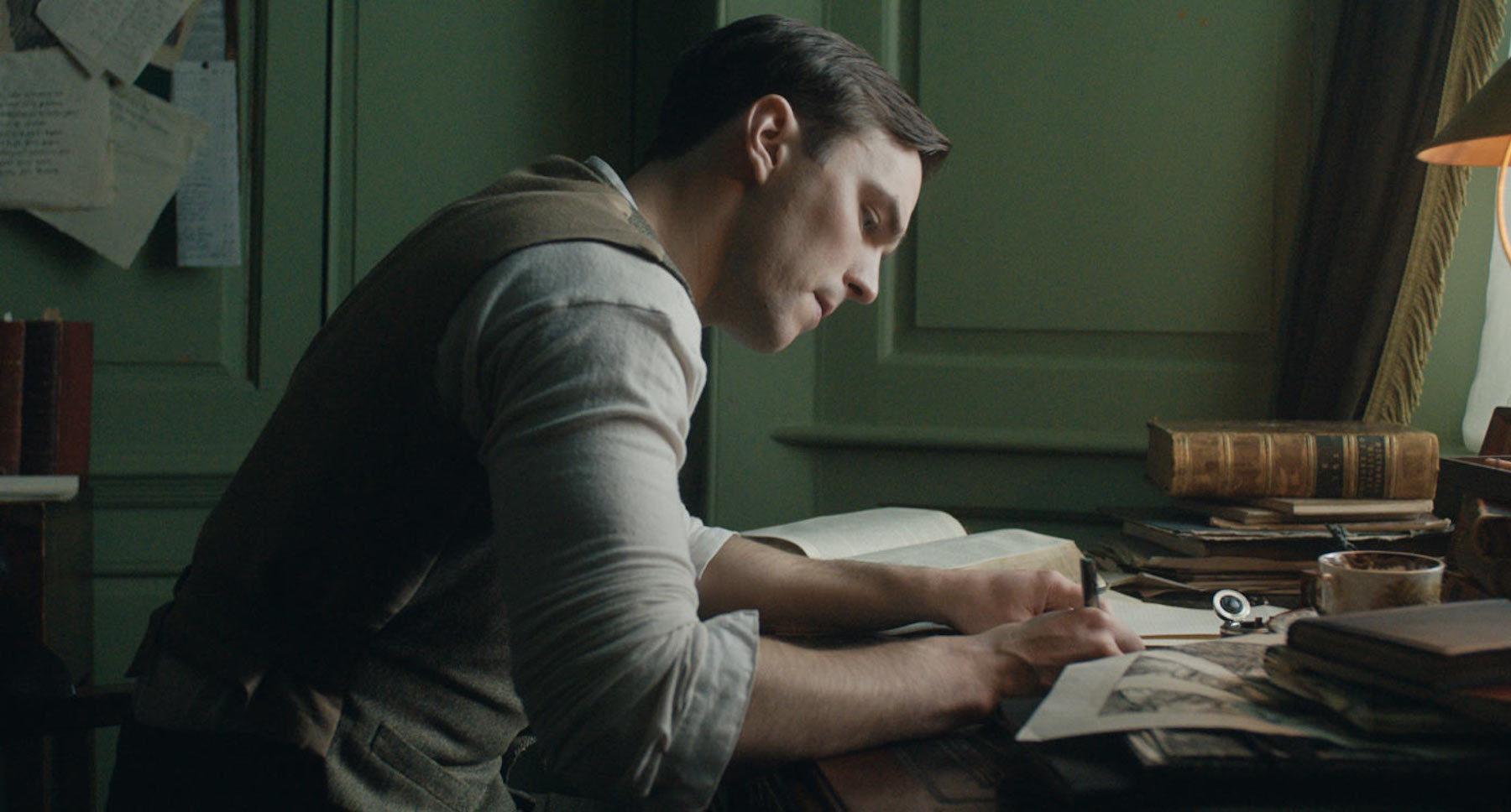 "Nicholas Hoult as Tolkien sitting at a desk writing in ""Tolkien"""