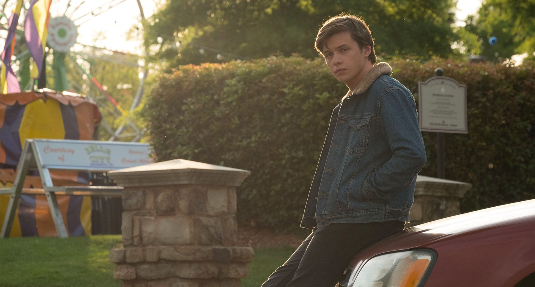 "Nick Robinson (as Simon) standing next to a car in ""Love, Simon"""