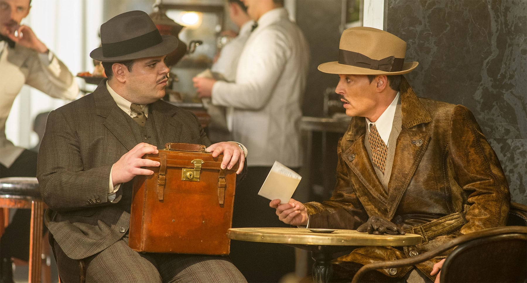 "Johnny Depp (as Edward Ratchett) and Josh Gad (as Hector MacQueen) sitting at a table in ""Murder on the Orient Express"""