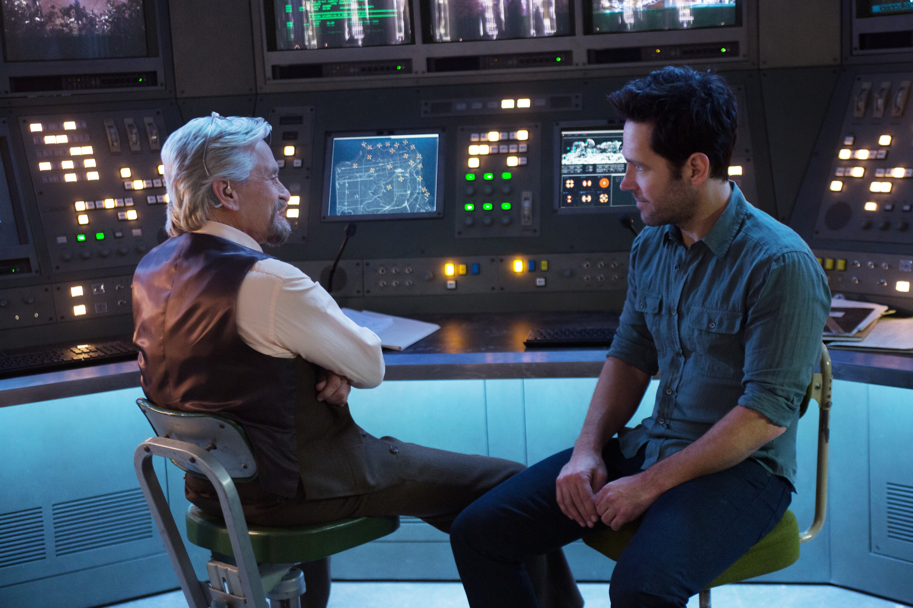 Paul Rudd (as Scott Lang) and Michael Douglas (as Hank Pym) sitting together in Ant-Man