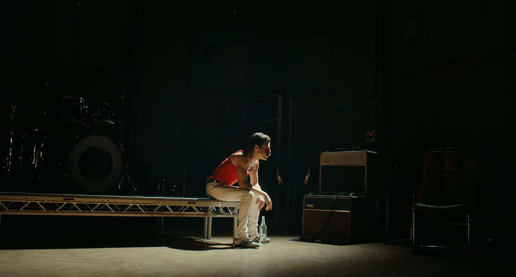 "Actor Rami Malek (as Freddie Mercury) sitting on the edge of a stage in the movie ""Bohemian Rhapsody"""