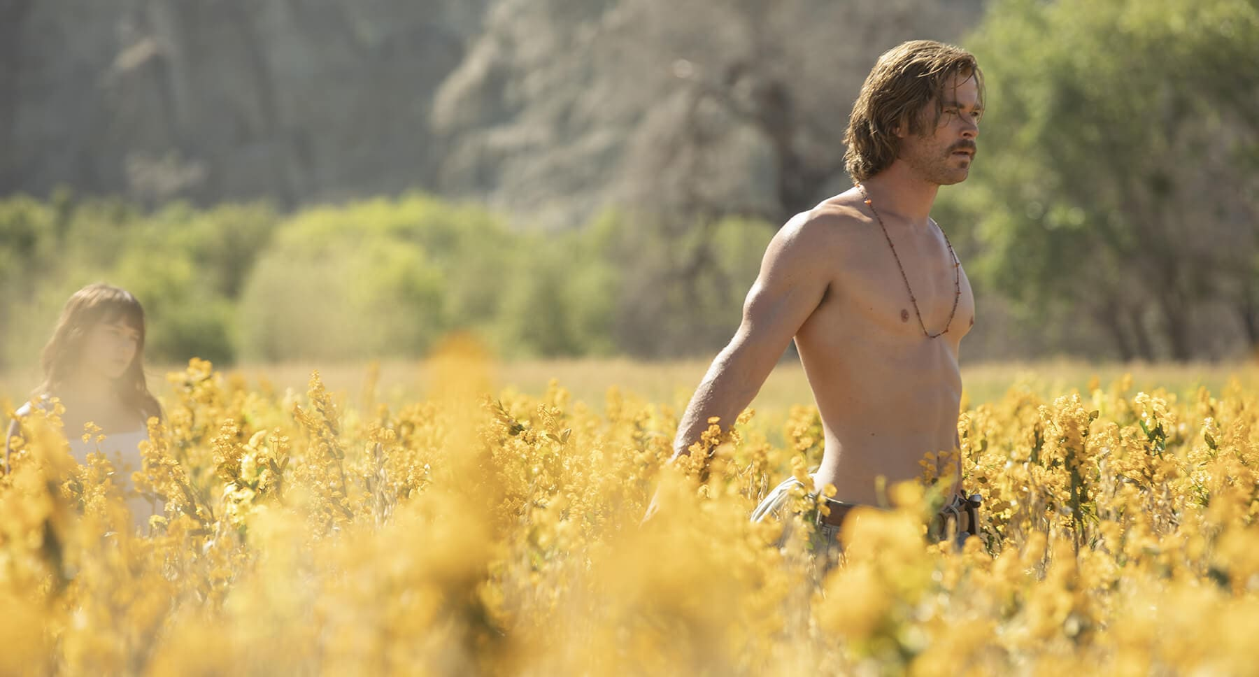 "Actor Chris Hemsworth (as Billy Lee) standing shirtless in a field in the movie "" Bad Times At The El Royale"""