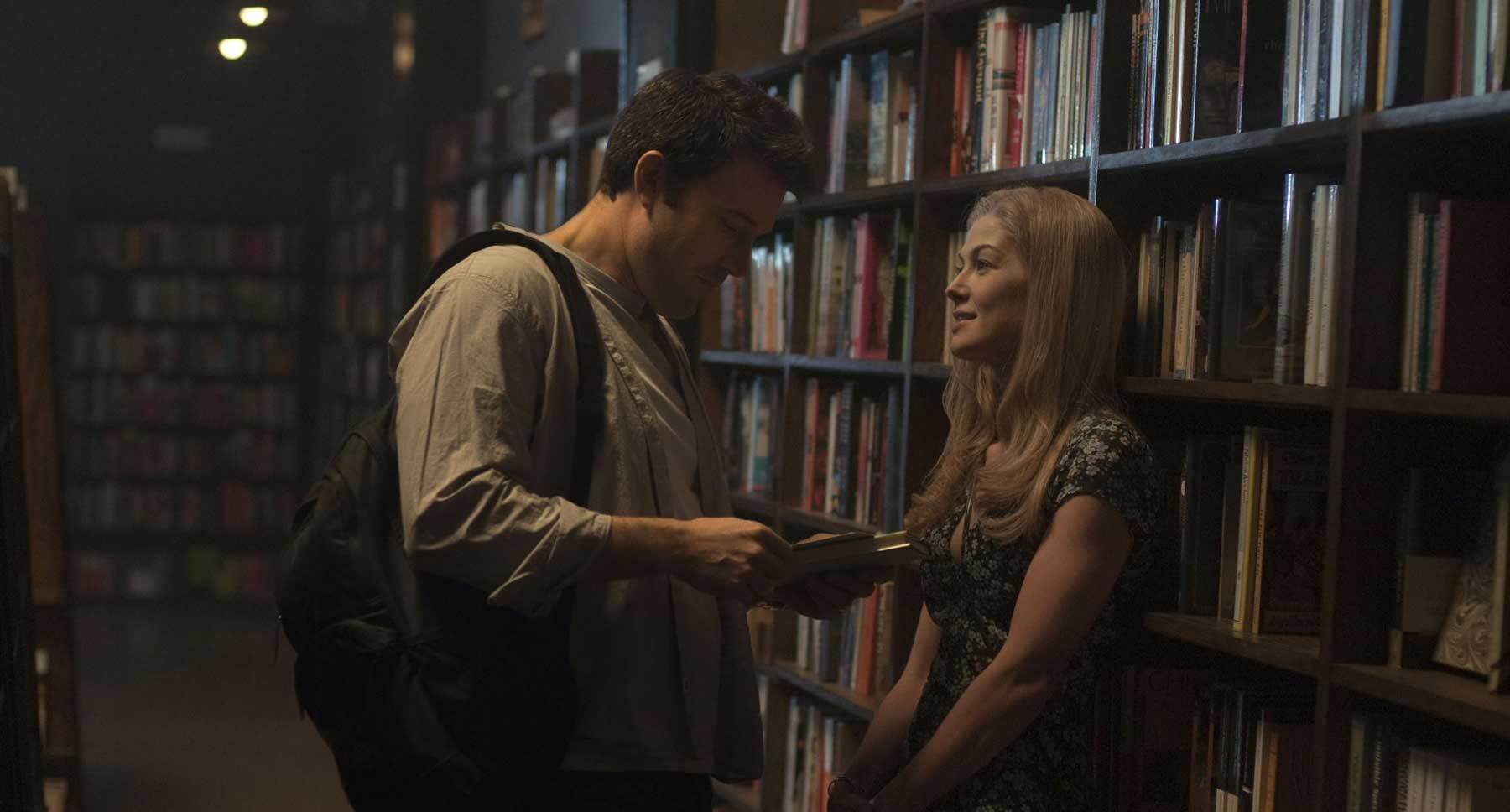 "Ben Affleck (Nick) and Rosamund Pike (Amy) talking in a library in ""Gone Girl"""