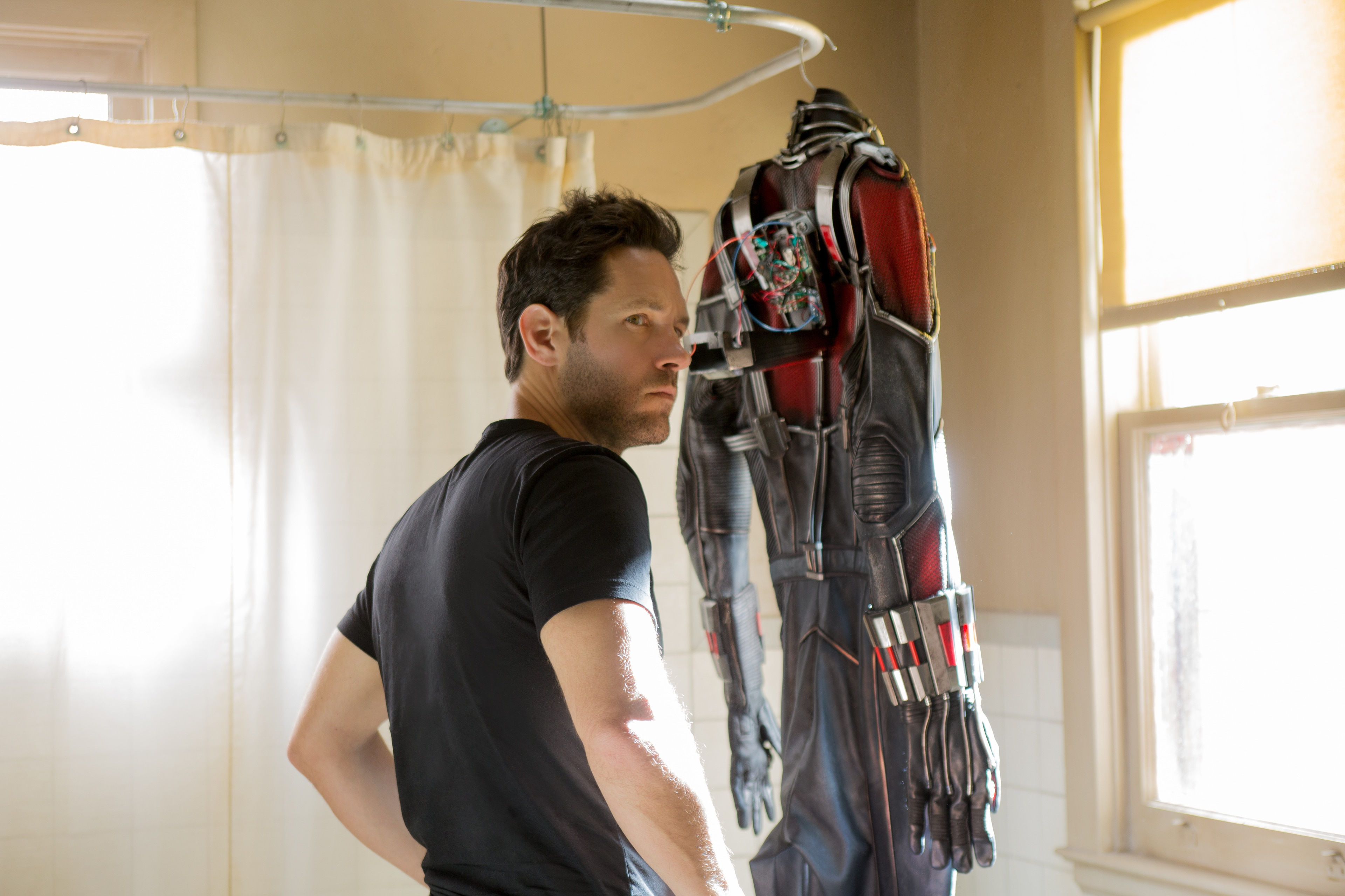 Paul Rudd (as Scott Lang) looking at the Ant-Man suit