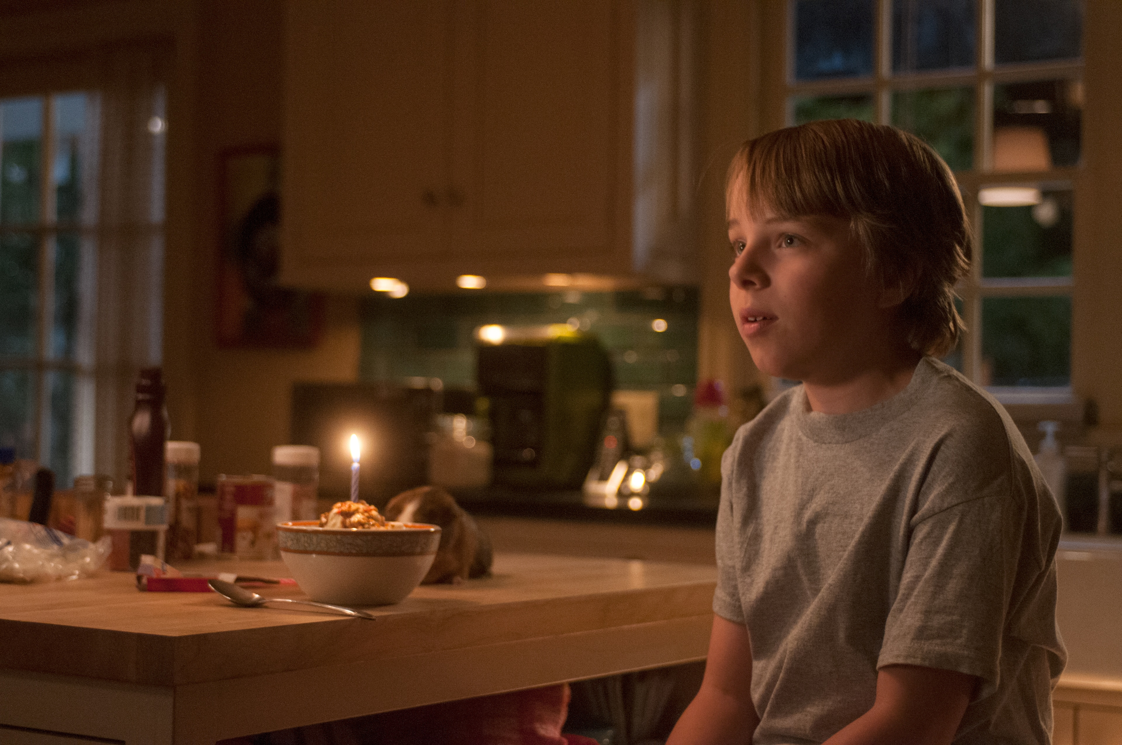 Ed Oxenbould as Alexander Cooper sitting in front of a bowl of ice cream with a lit candle in it