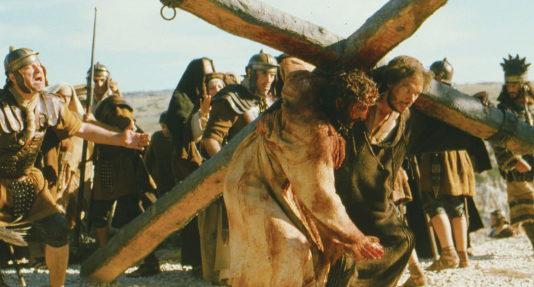 "Simon of Cyrene (Jarreth Merz) helps Jesus (Jim Caviezel) carry the cross in ""The Passion of the Christ"""