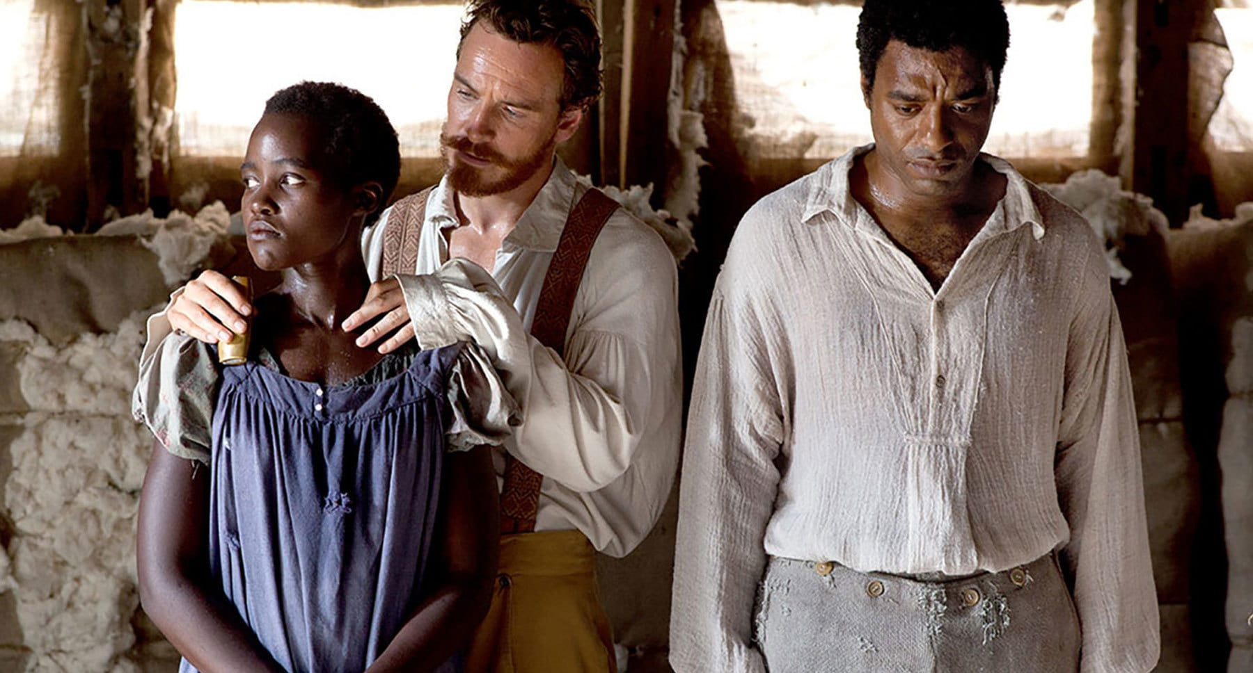 "Actors Lupita Nyong'o (Patsy), Michael Fassbender (Edwin Epps), and Chiwetel Ejiofor (Solomon Northrup) standing in the film ""12 Years A Slave"""