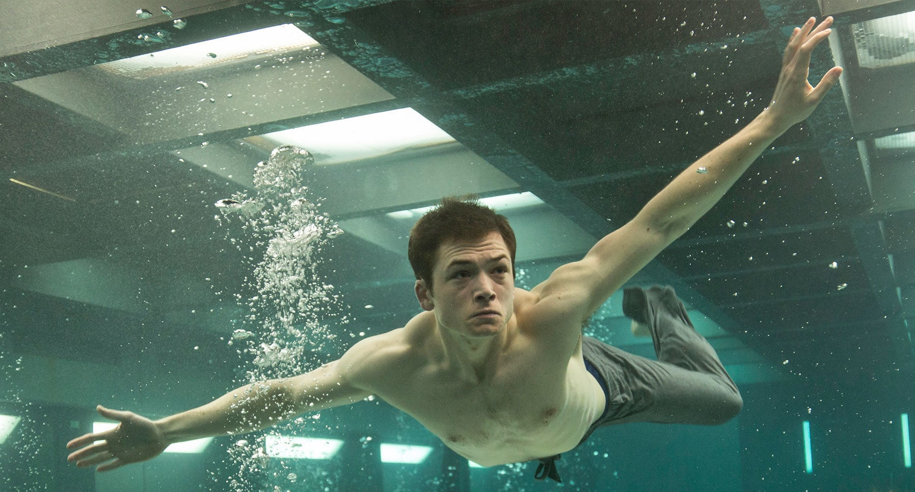 "Taron Egerton (as Gary 'Eggsy' Unwin) swimming in a flooded room in ""Kingsman: The Secret Service"""