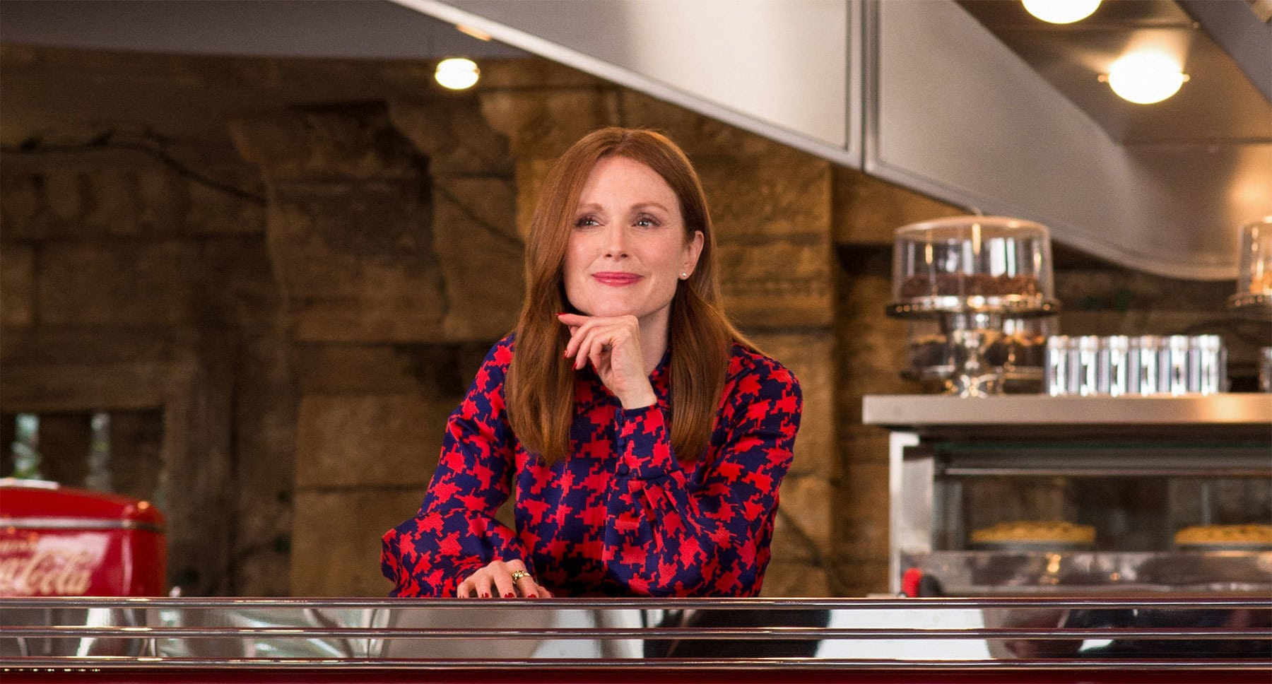 Julianne Moore (as Poppy) sitting at a counter in Kingsman: The Golden Circle
