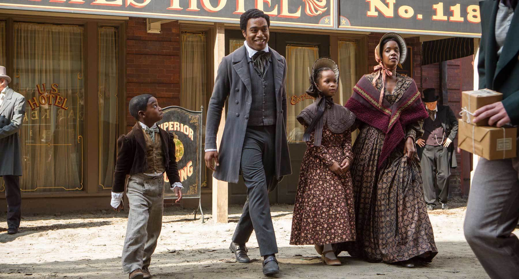 "Actors Chiwetel Ejiofor, Kelsey Scott, Quvenzhané Wallis, and Cameron Zeigler as Northrup family in suits and dresses in the film ""12 years A Slave"""