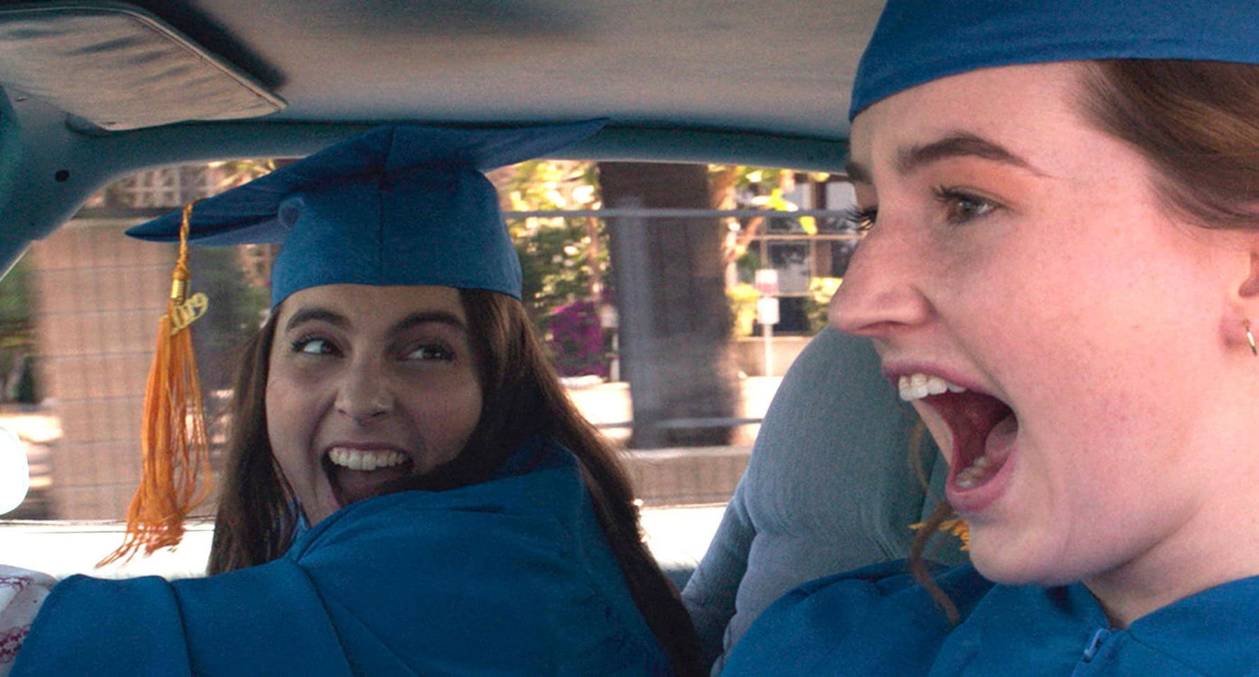 "Actors Kaitlyn Dever (as Amy) and Beanie Feldstein	(as Molly) screaming in a car wearing cap and gown in the movie ""Booksmart"""