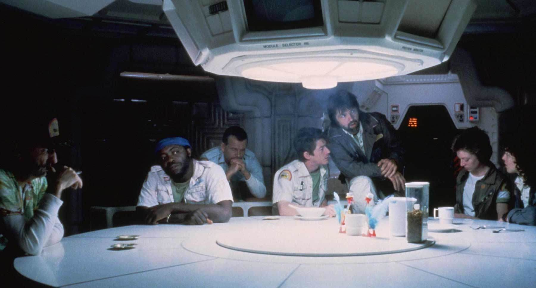 "Actors Tom Skerrit, Sigourney Weaver, Veronica Cartwright, Harry Dean Stanton, John Hurt (Kane), Ian Holm and Yaphet Kotto at a table in the movie ""Alien"""