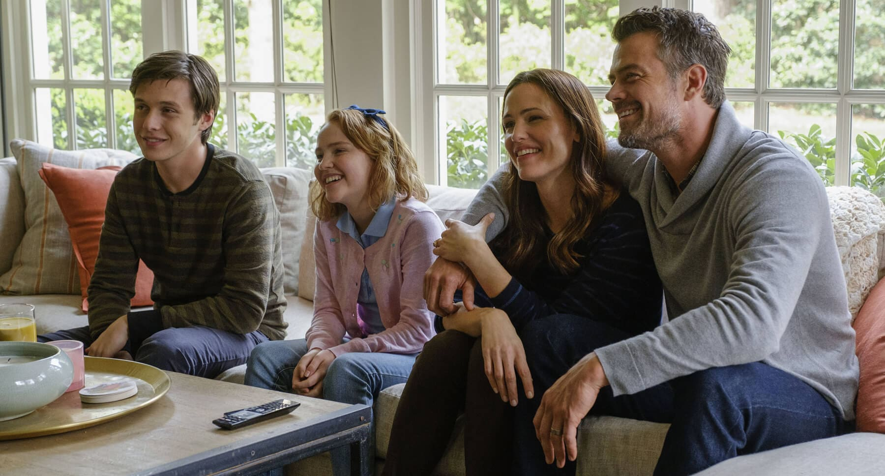 "Jennifer Garner (as Emily), Josh Duhamel (as Jack), Nick Robinson (as Simon), and Talitha Eliana Bateman (as Nora) sitting on a sofa in ""Love, Simon"""