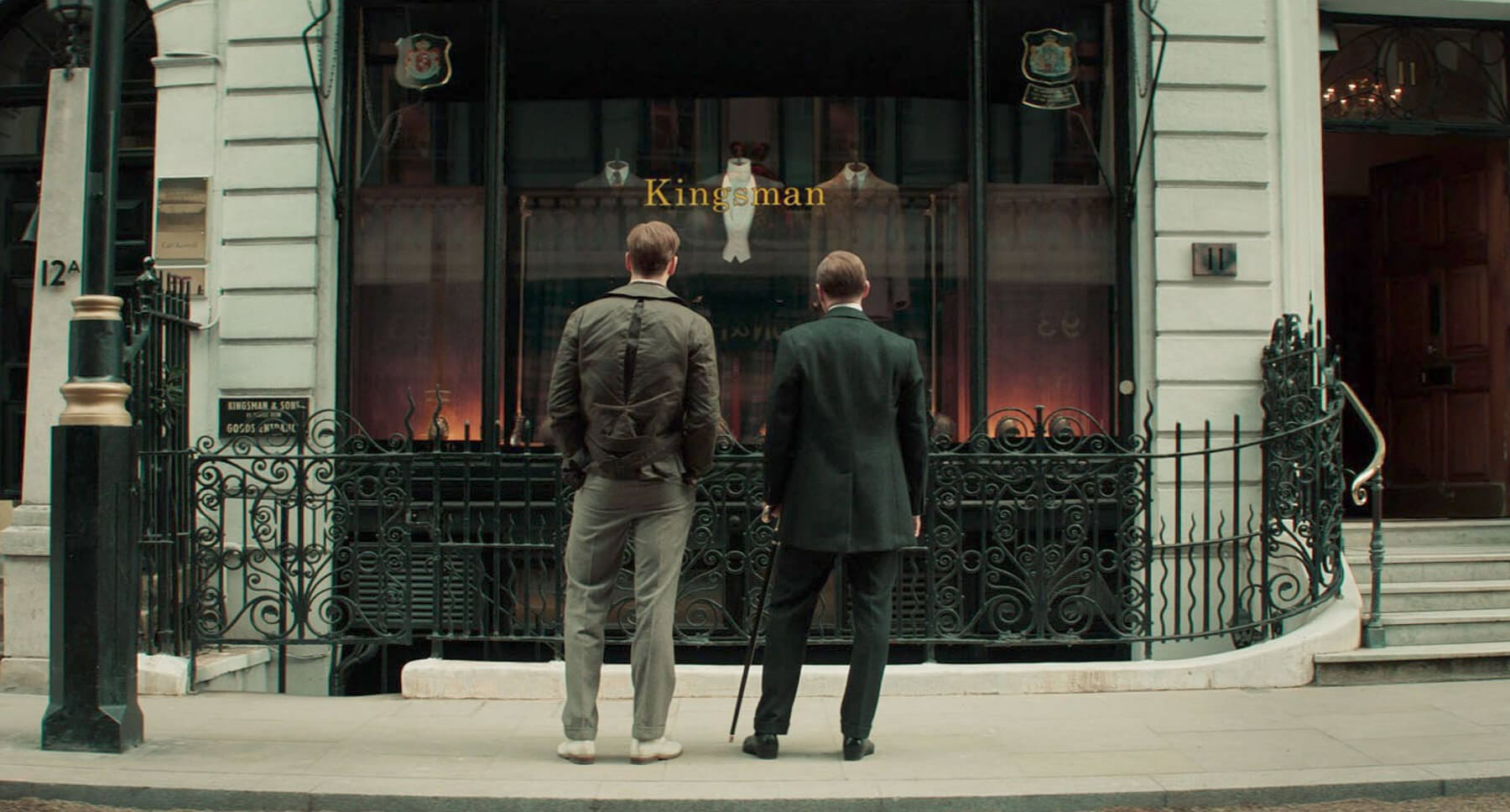 "Two men on the sidewalk looking into a Kingsman shop from the movie ""The King's Man"""
