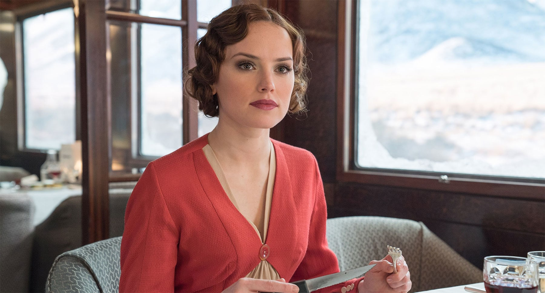 "Daisy Ridley (as Mary Debenham) sitting at a dining table in ""Murder on the Orient Express"""