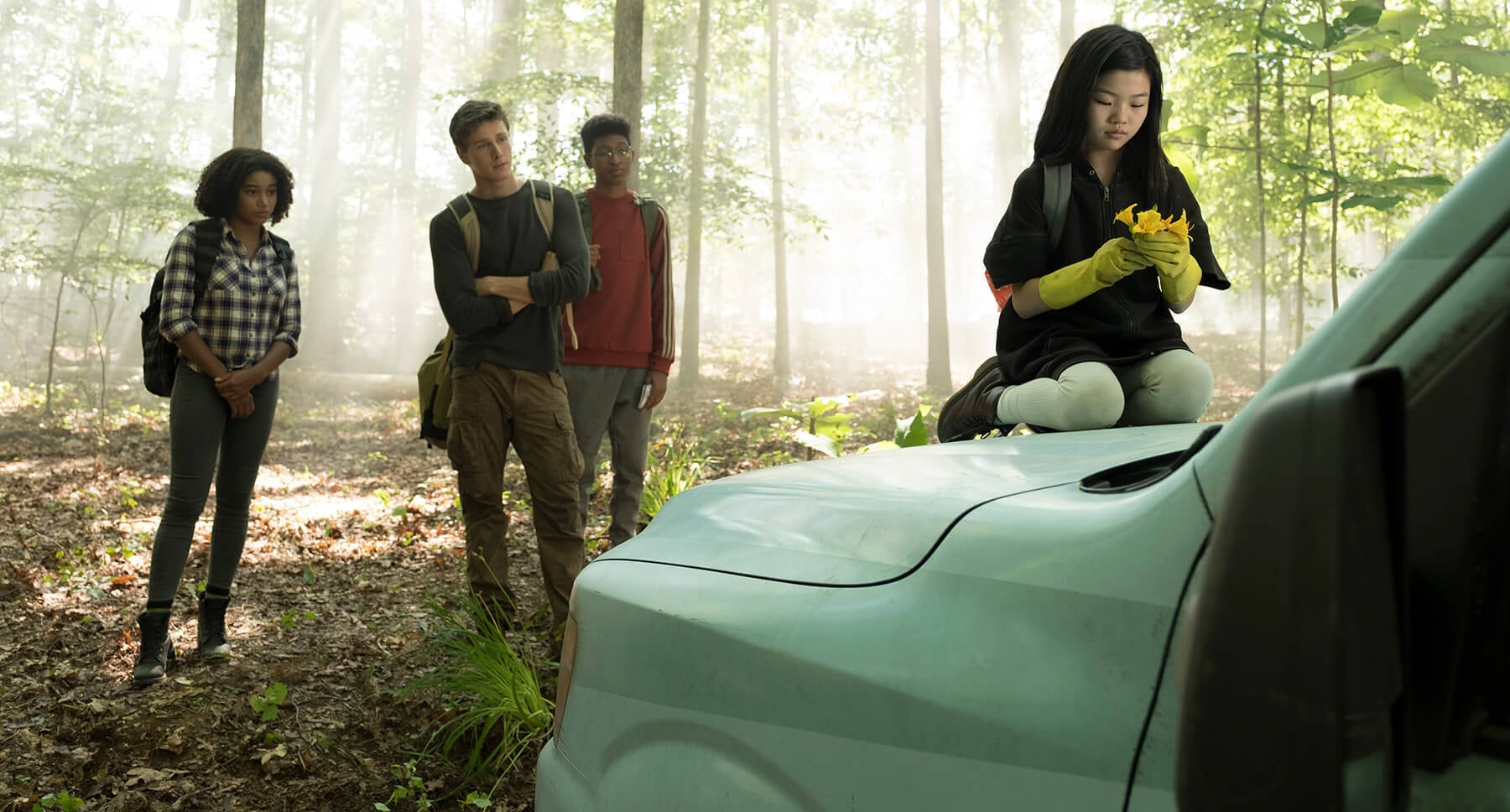 "Actors Skylan Brooks, Amandla Stenberg, Harris Dickinson and Miya Cech near a car in the movie ""The Darkest Minds"""