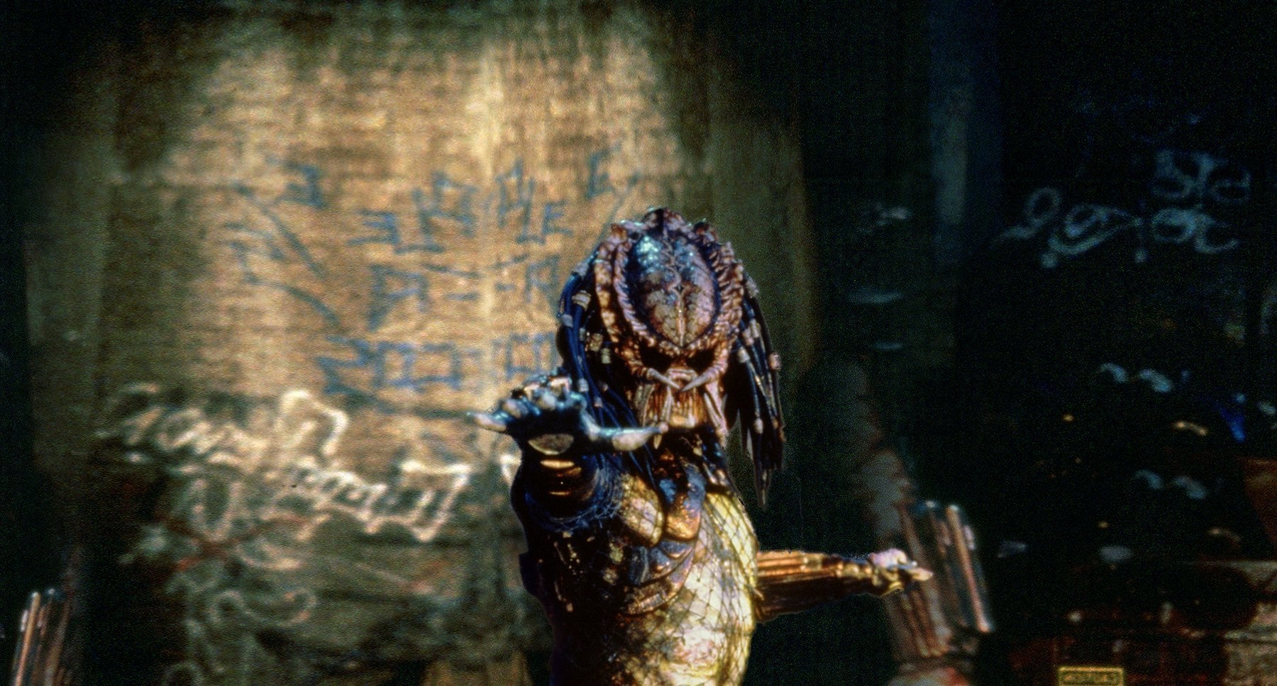 "The predator standing next to a wall in the movie ""Predator 2"""