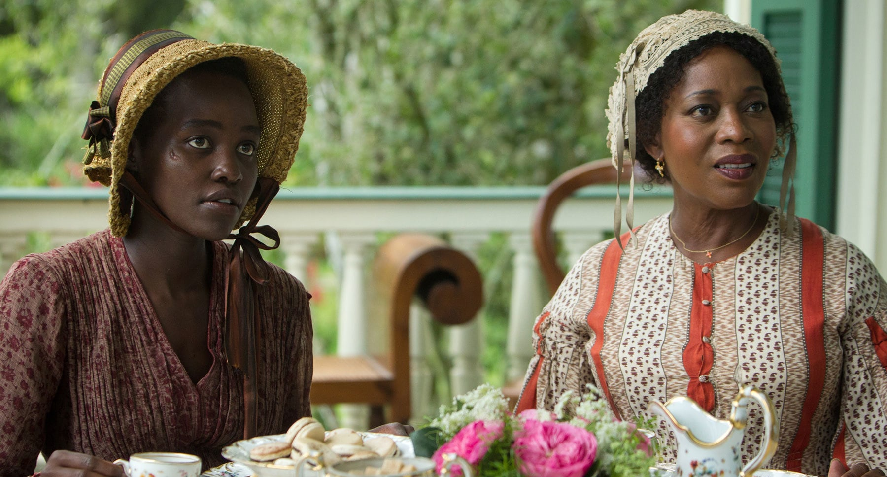 "Actors Lupita Nyong'o (Patsy) and Alfre Woodard (Mistress Shaw) having tea at a table in the film ""12 Years A Slave"""