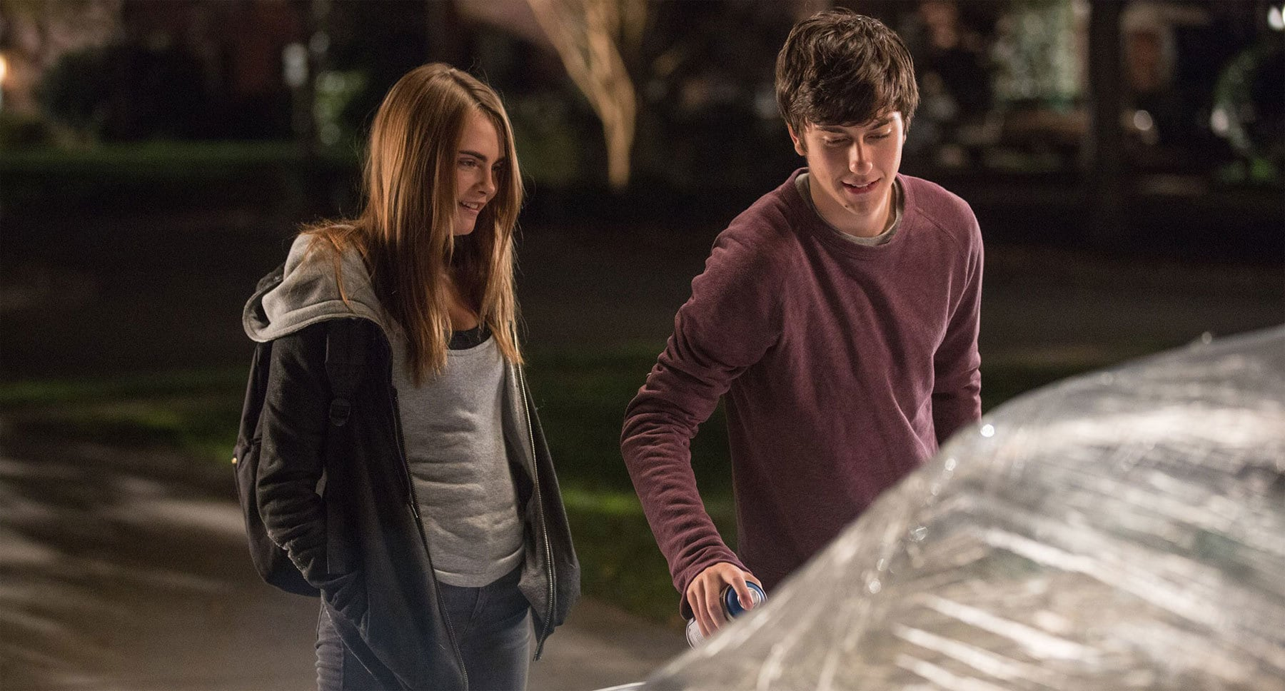 "Nat Wolff (as Quentin) and Cara Delevingne (as Margo) spray painting a car in ""Paper Towns"""