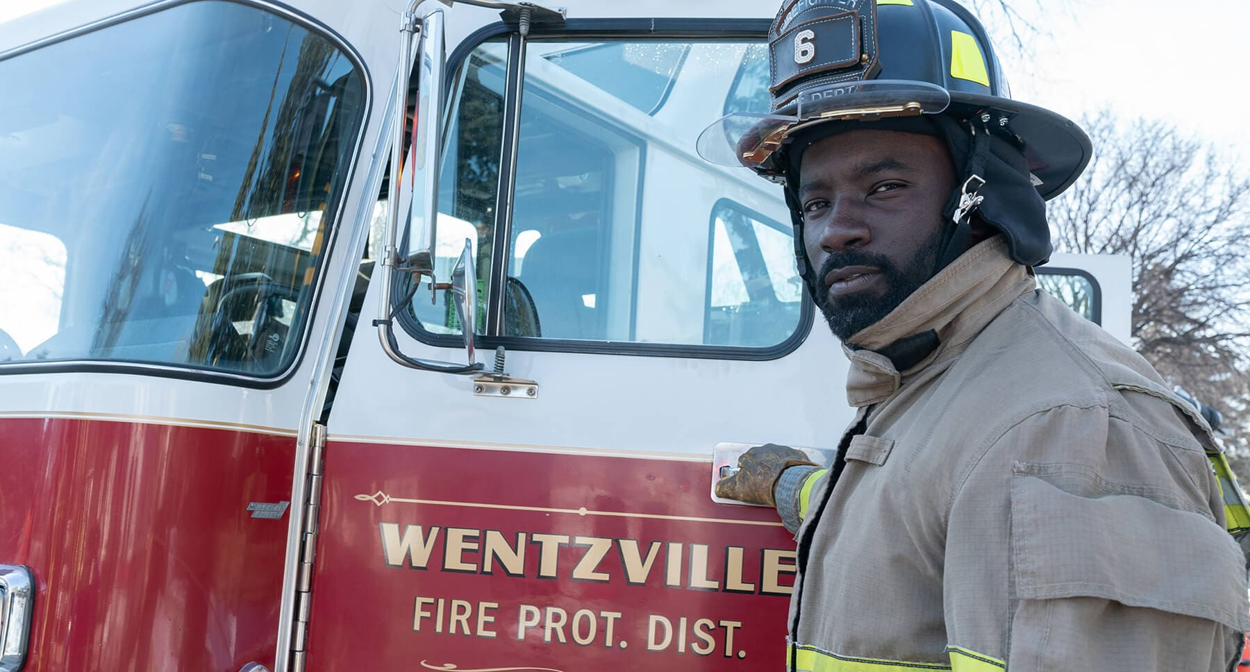 Actor Mike Colter (as Tommy Shine) standing in front of a fire truck in fire fighter gear in the film :Breakthrough""
