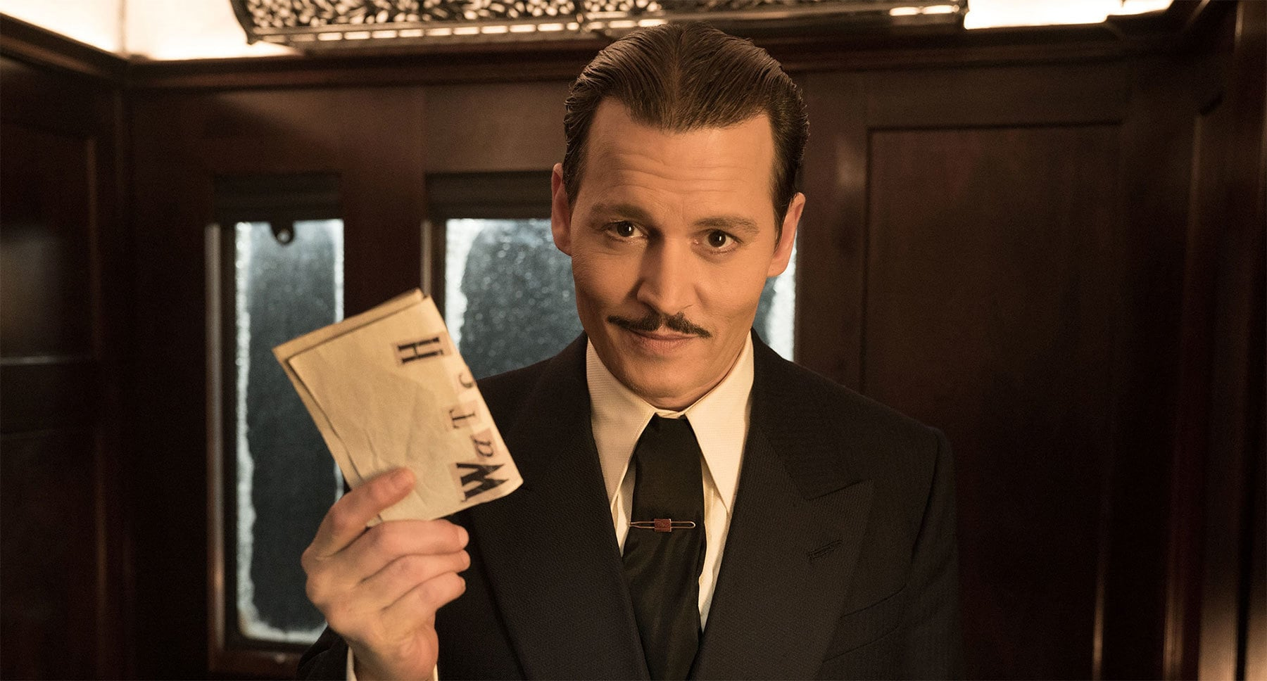 "Johnny Depp (as Edward Ratchett) holding a piece of paper in his hand in ""Murder on the Orient Express"""
