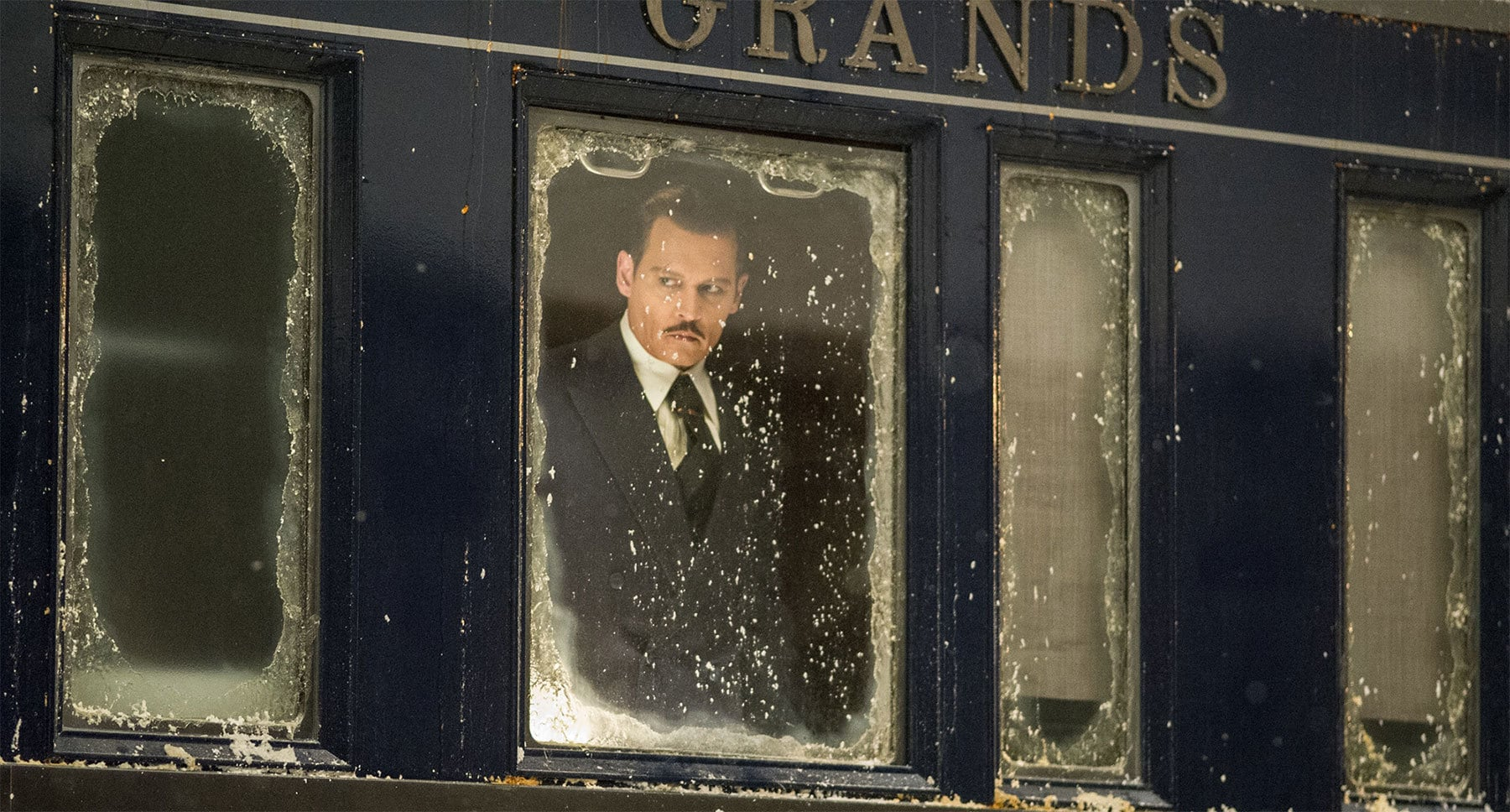 "Johnny Depp (as Edward Ratchett) looking out a snow covered train window in ""Murder on the Orient Express"""