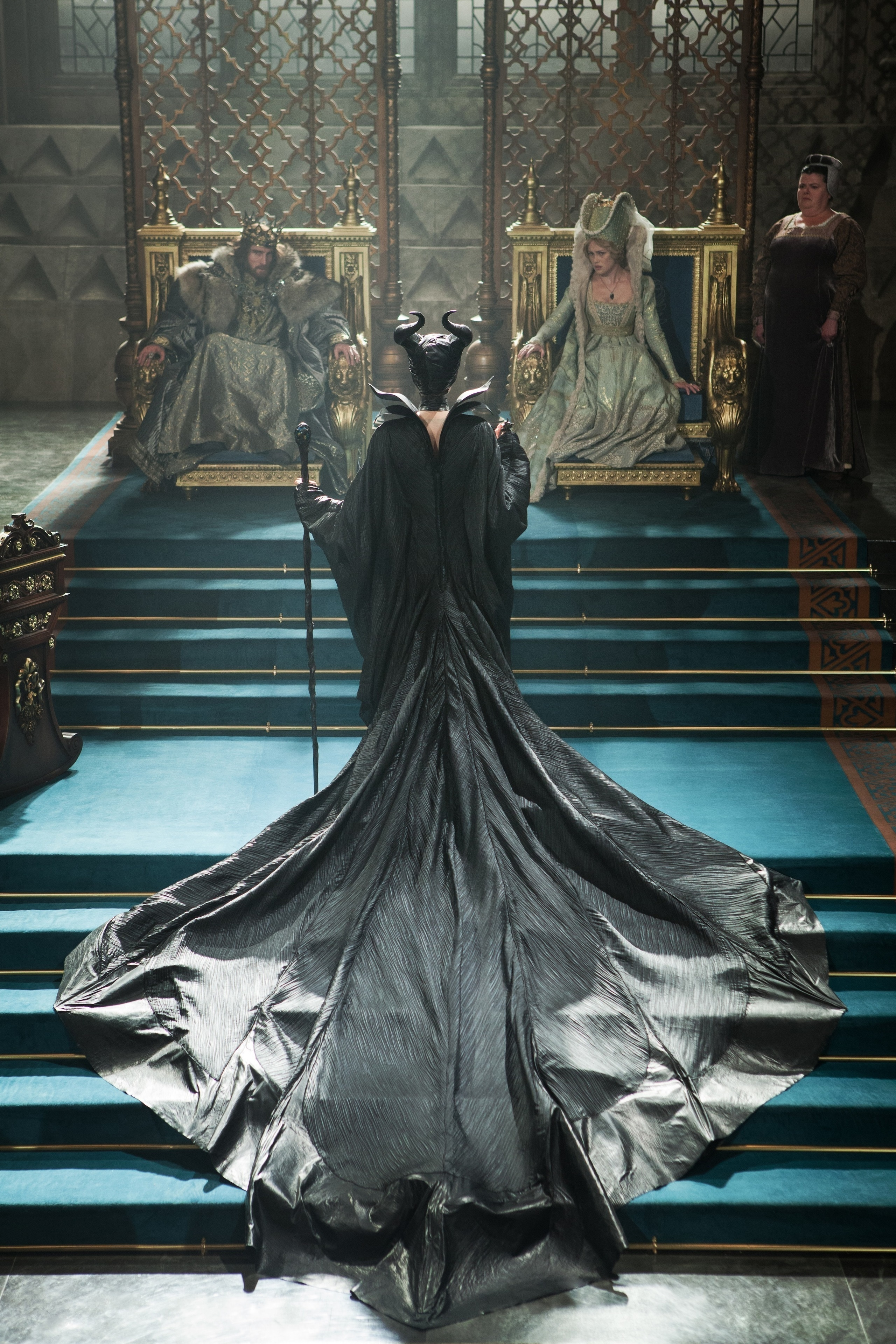 "Angelina Jolie as Maleficent standing before Sharlto Copley as Stefan, Hannah New as Princess Leila, and Sarah Flind as Princess Leila's Handmaiden in ""Maleficent"""