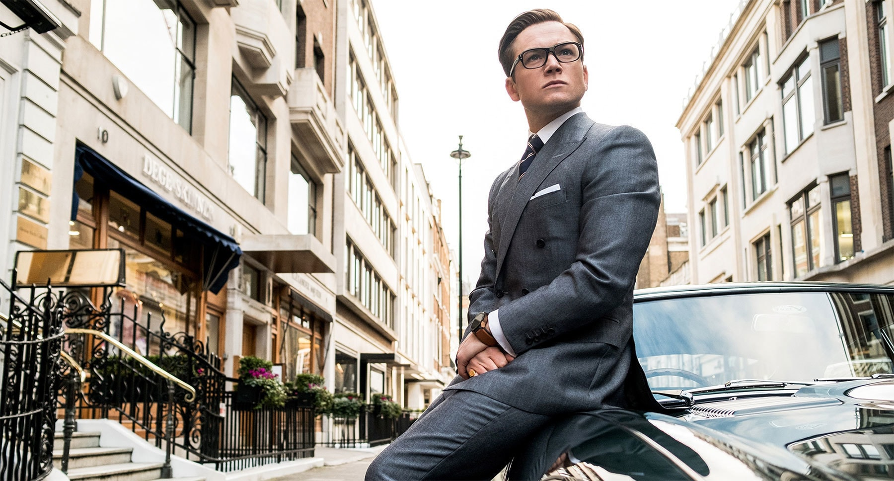 "Taron Egerton (as Eggsy) leaning on the side of a car in ""Kingsman: The Golden Circle"""