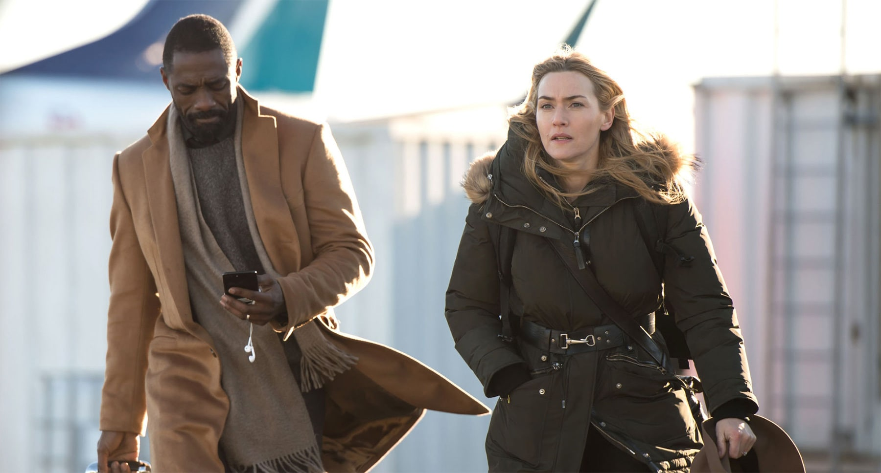 "Idris Elba (as Ben Bass) and Kate Winslet (as Alex Martin) walking in the movie ""The Mountain Between Us"""