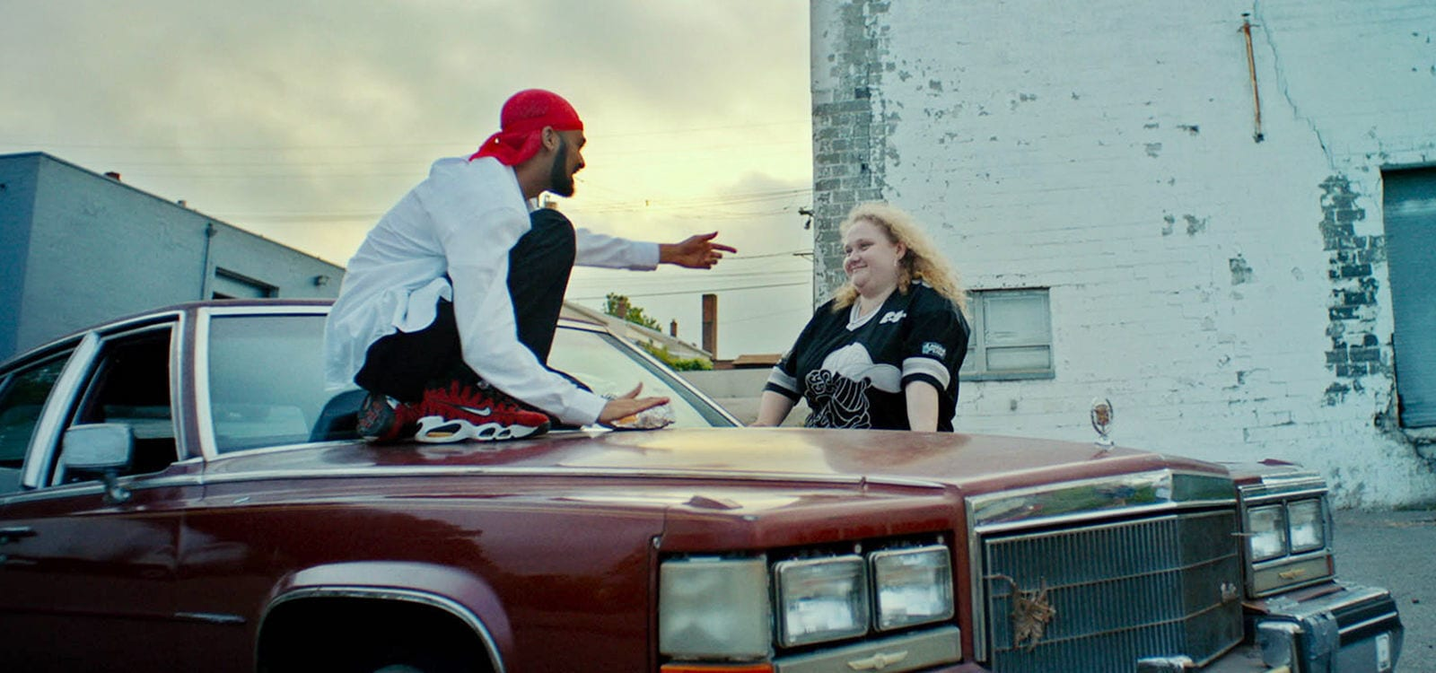 "Danielle Macdonald (as Patti) and Siddharth Dhananjay (as Jheri) chatting in the movie ""Patti Cake$"""
