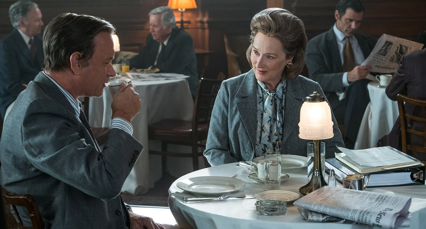 "Tom Hanks and Meryl Streep sitting at a table in ""The Post"""